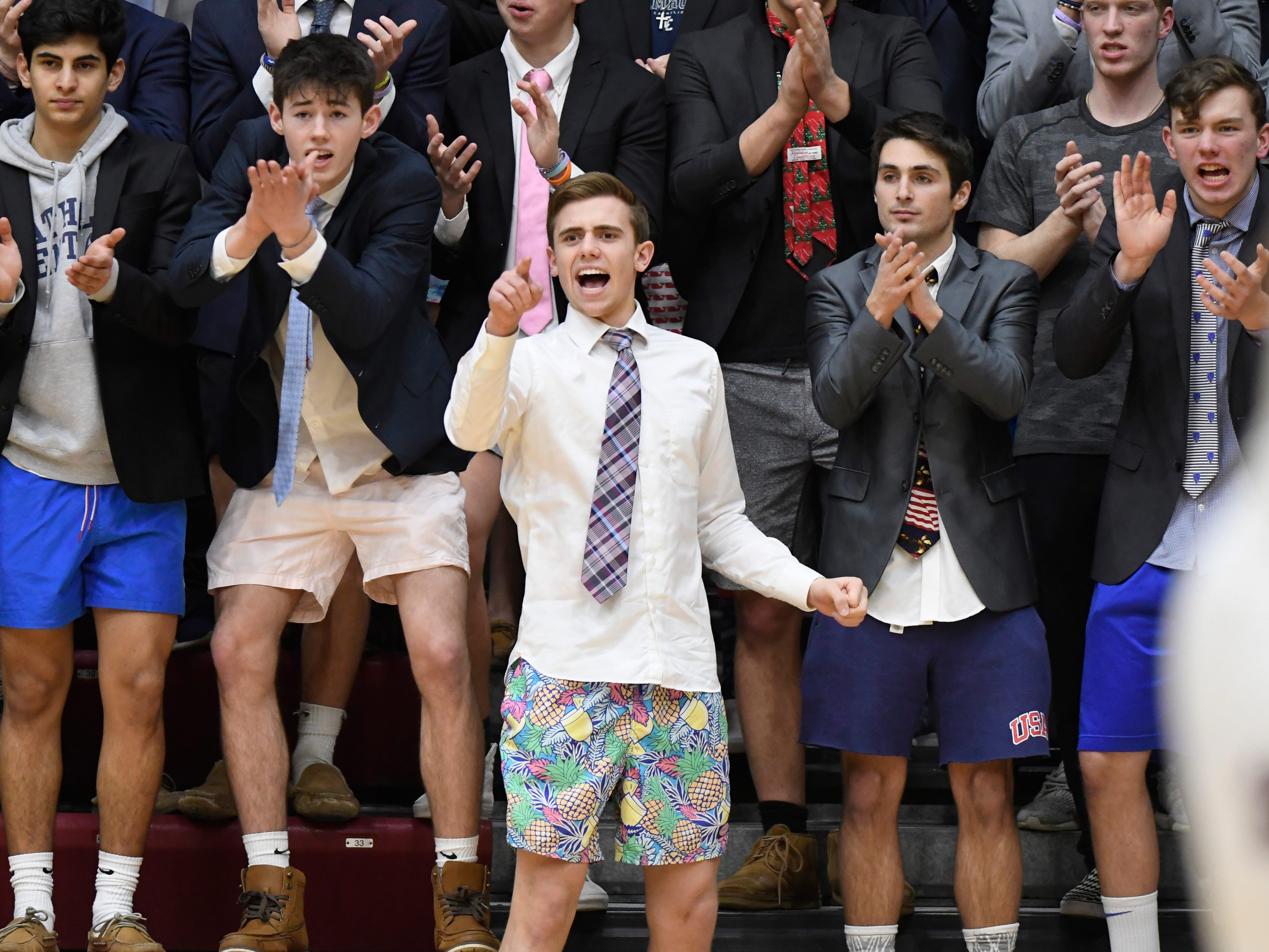 Detroit Catholic Central students, dressed in half formal attire, cheer on their team as they played against Detroit Jesuit during the fourth quarter.