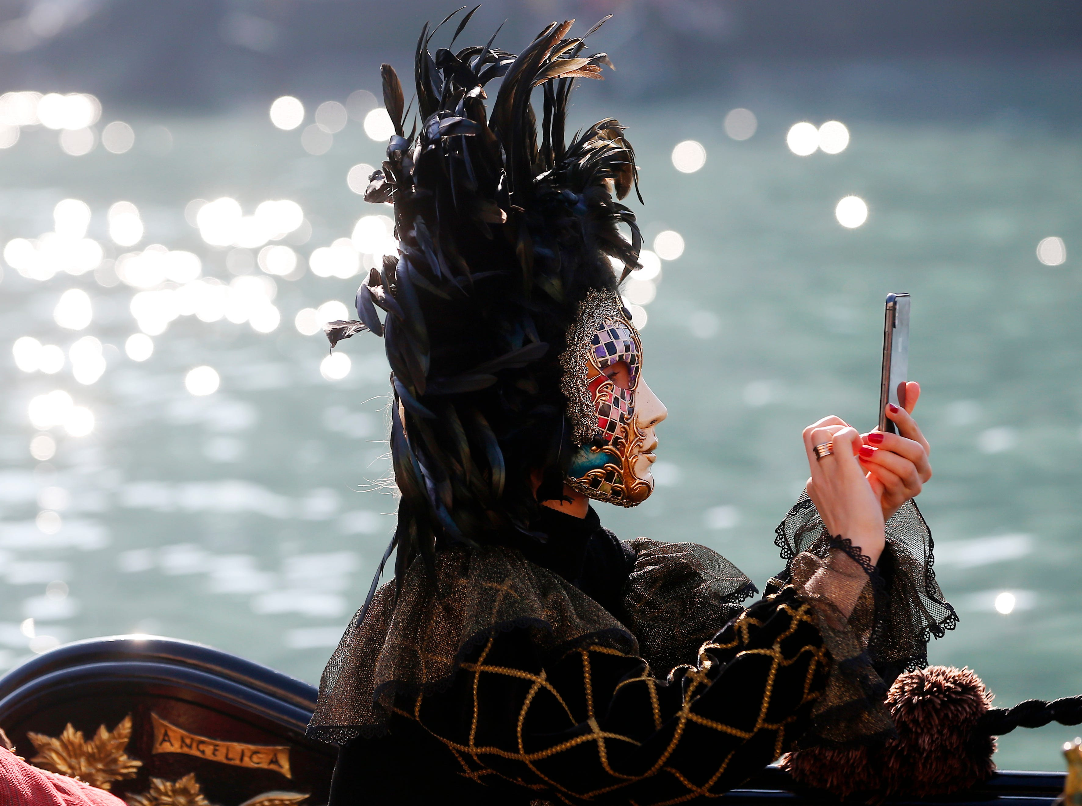 A masked woman checks her smartphone while sitting in a gondola during the water parade, part of the Venice Carnival, in Venice, Italy, Sunday, Feb. 17, 2019. The Venice carnival in the historical lagoon city attracts people from around the world.