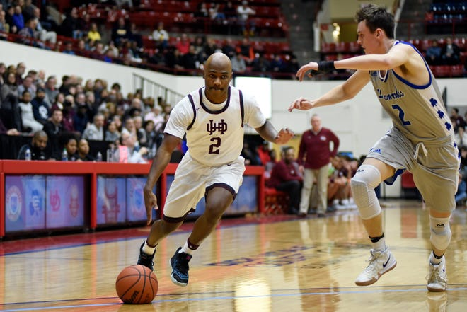U. of D Jesuit guard Caleb Hunter (2), left, dribbles against Detroit Catholic Central's Brendan Downs (2) during the first quarter.