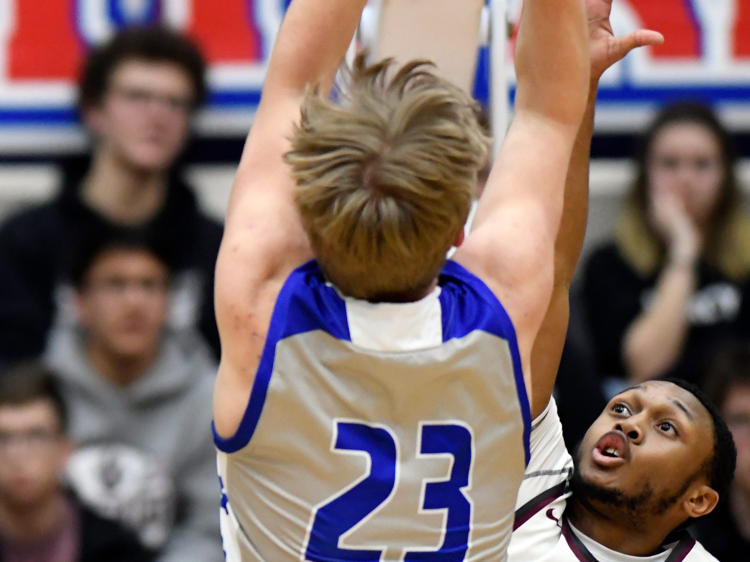 Detroit Catholic Central's Jacob Woebkenberg (23) goes up for a shot over U. of D Jesuit guard Jordan Montgomery (3) during the first quarter.