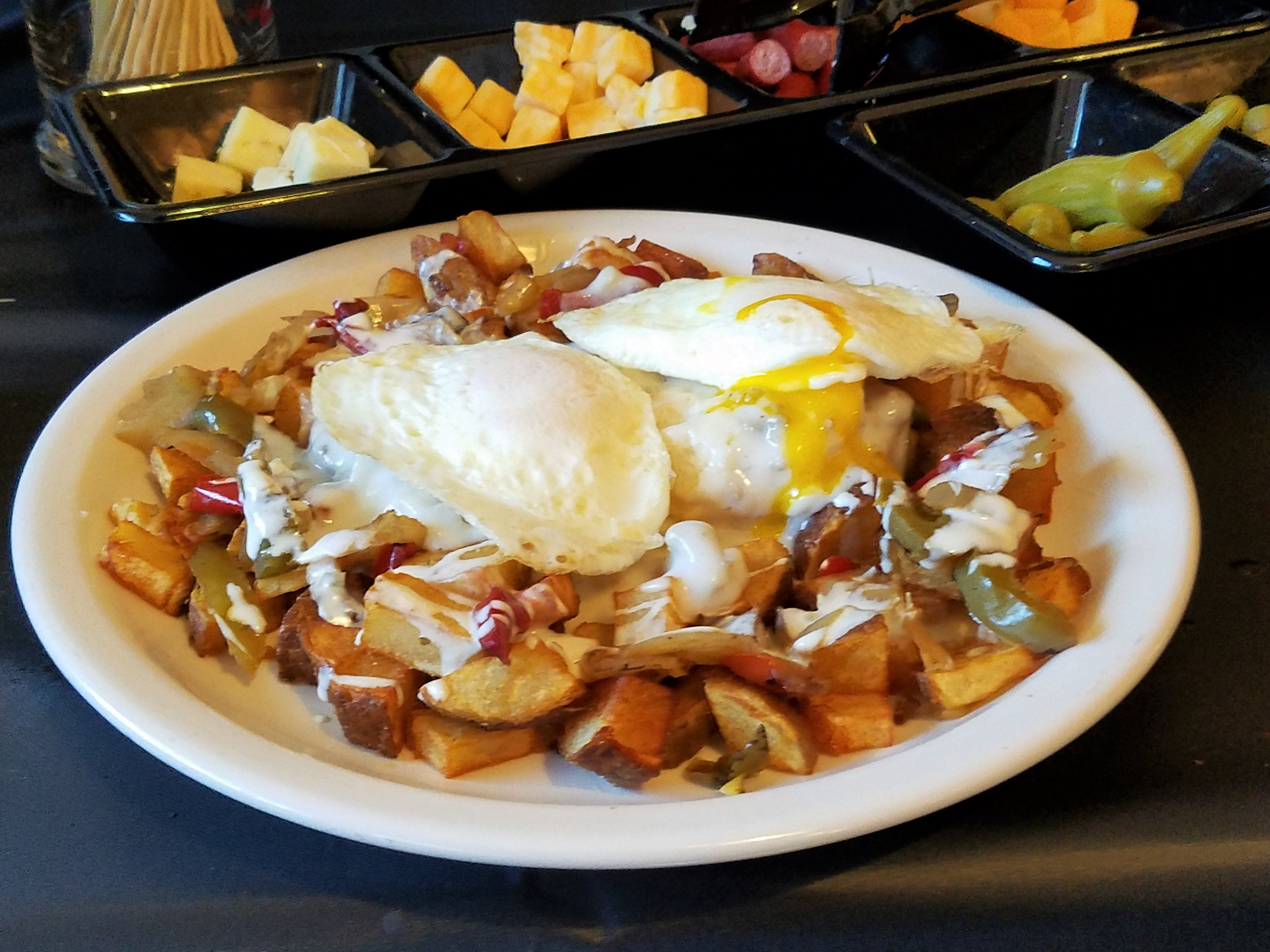 The Big Al plate at Hawg N Sauce Saturday brunch: home fries with peppers, queso, biscuits with gravy and two eggs your way.