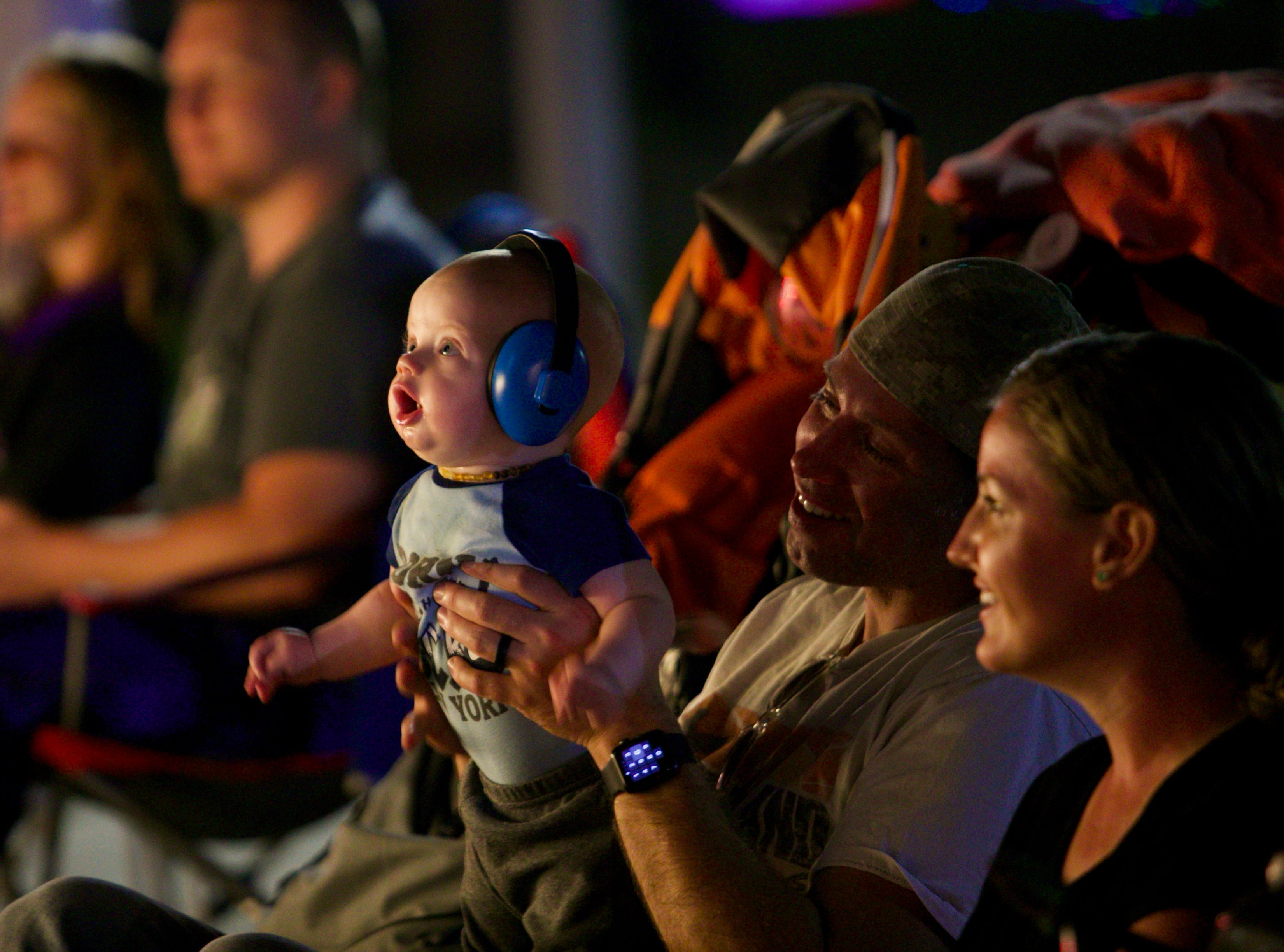 Calvin Cato, 5 months, watches the Edison Festival of Light Grand Parade with his parents Steven and Kiersten Cato.