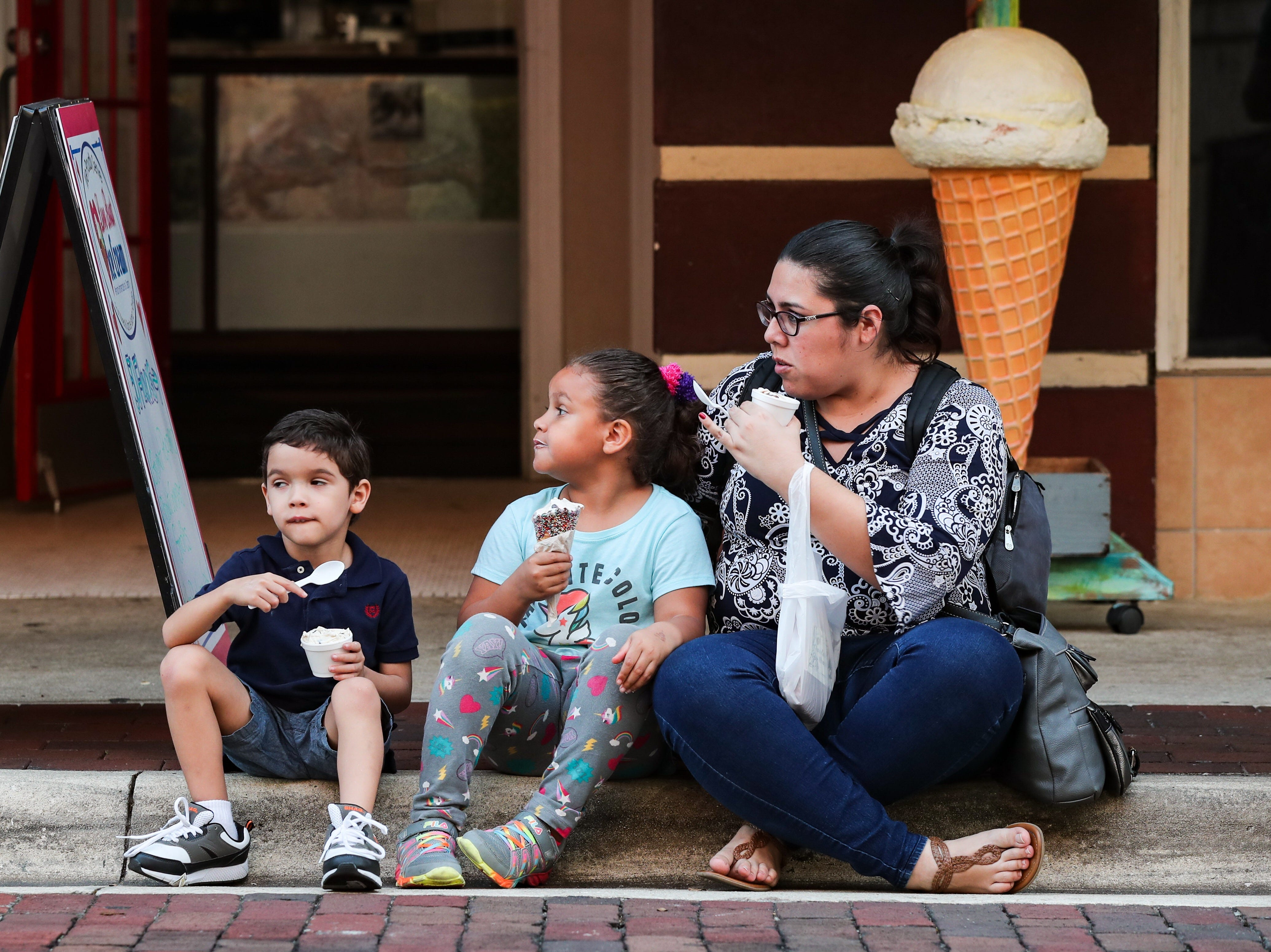 Cesar 4,  Victoria 5, and their mother Karla Hidilgo of Lehigh enjoy some ice cream. You showed up early for the Edison Festival of Lights Grand Parade in Downtown Fort Myers, Florida. What did you munch on while you waited for the parade to start?
