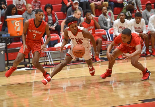 Greenville's Quentin Johnson, center, battles for a loose ball with Westwood's Breon Lewis, left, and Ta'Jay Dunlop. Johnson led the Red Raiders with 15 points Saturday.