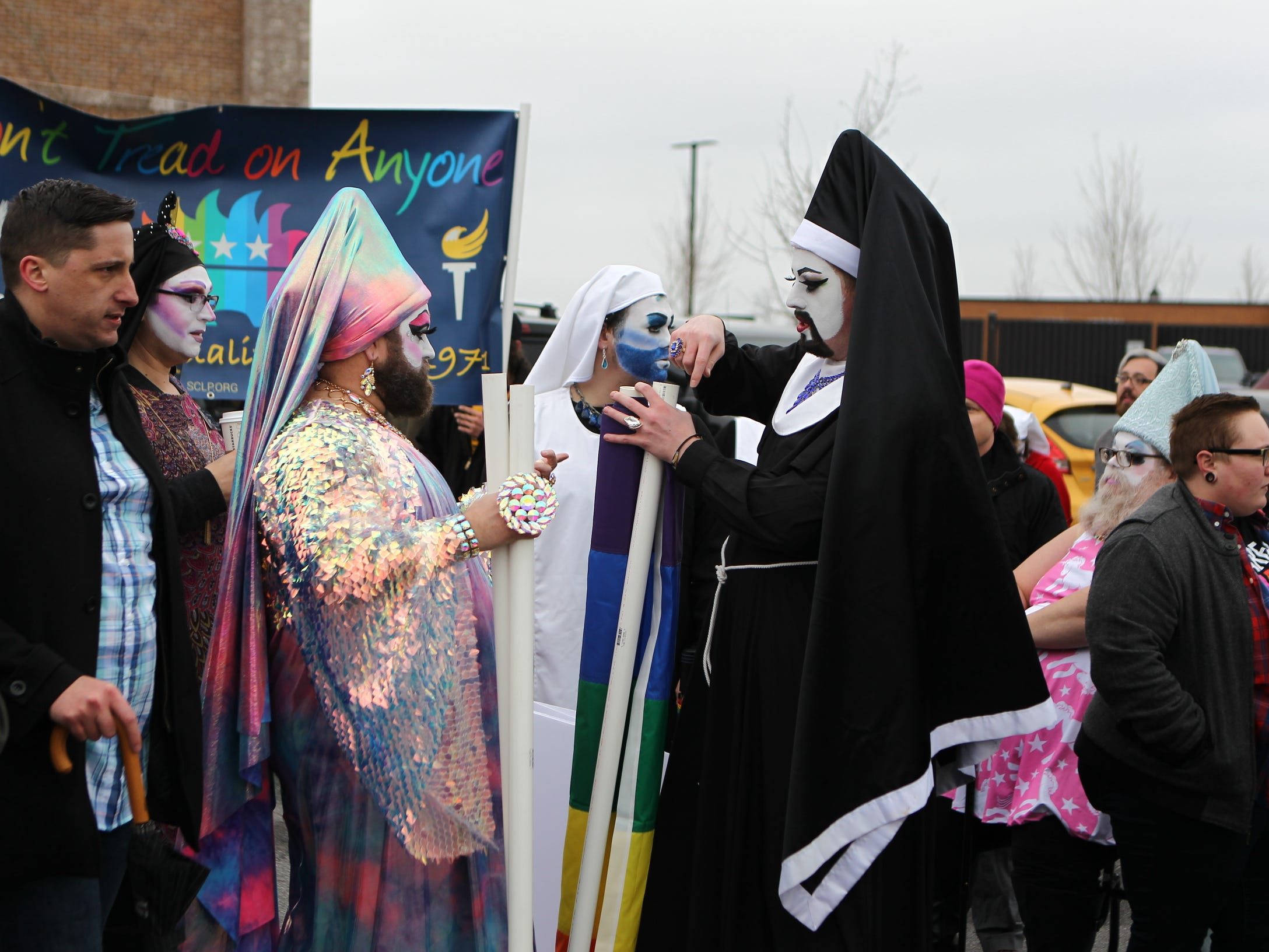 Two drag queens distribute rainbow flags in support of the Drag Queen story hour at Five Forks library on Sunday, Feb. 17, 2019.