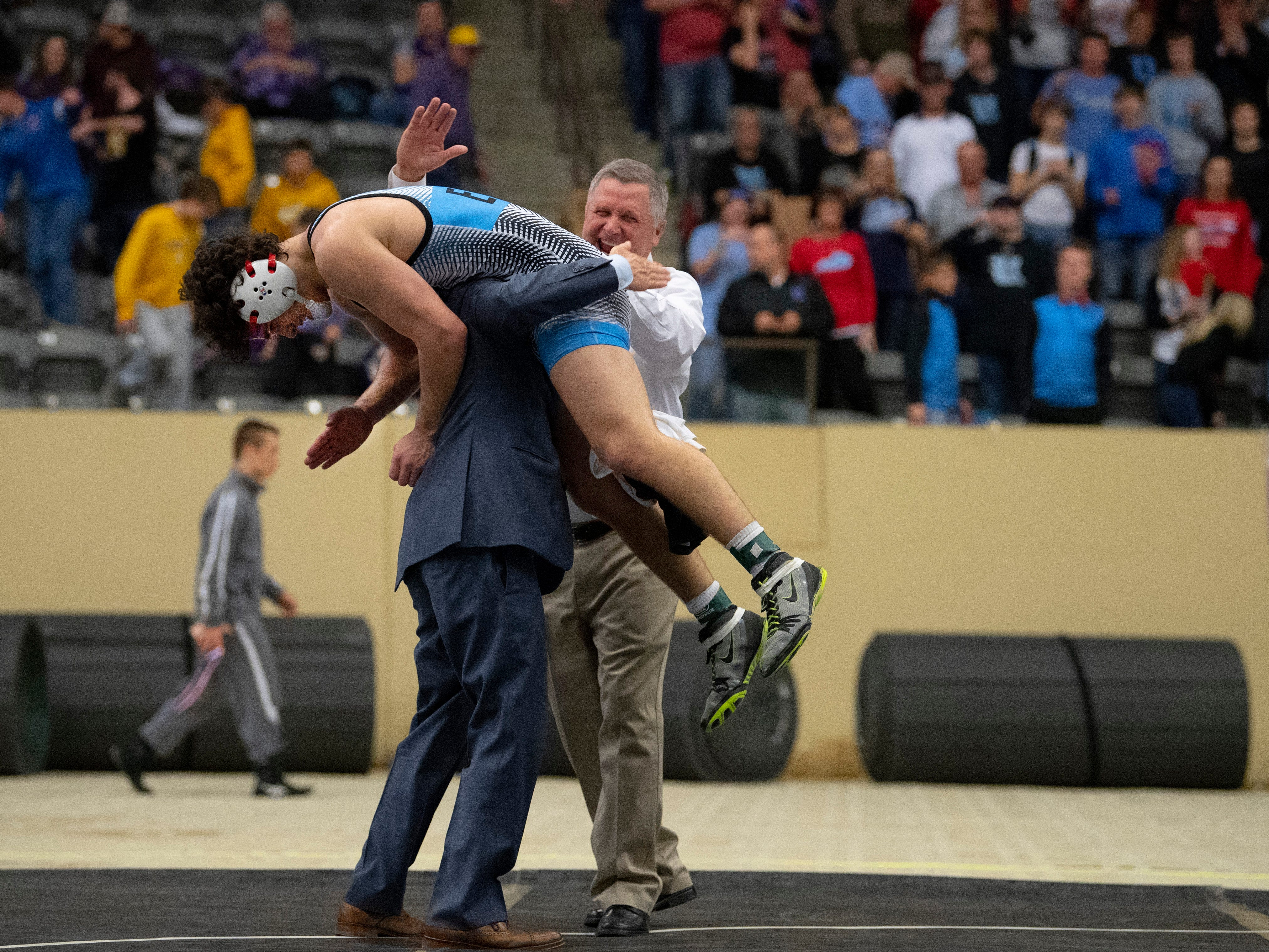 Micah Ervin gets a celebratory lift from his dad and coach, Robert Ervin, as his uncle and coach, Tim Ervin, gives him a slap on the back after winning the 170-pound state championship at the KHSAA State Wrestling Championships at the Alltech Arena in Lexington, Ky., Saturday afternoon.