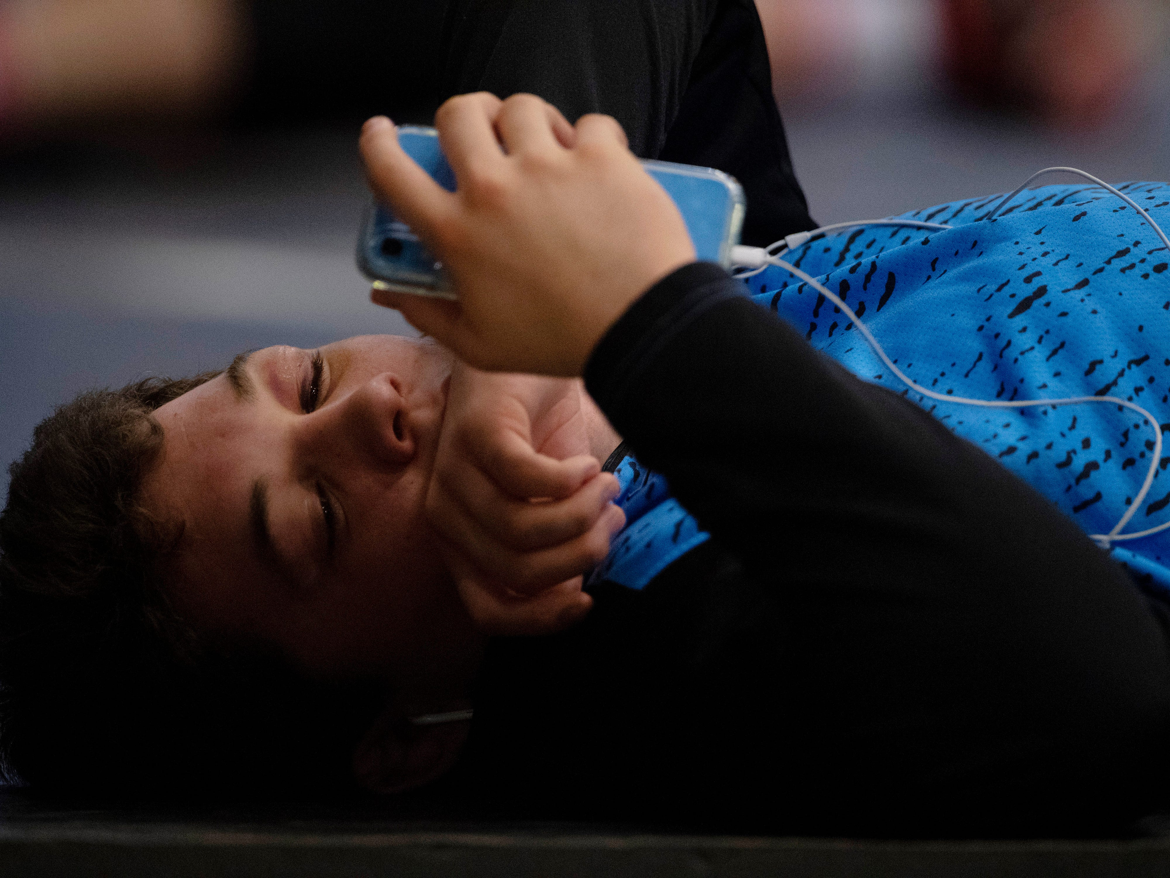 Union County's Mathias Ervin listens to some tunes on the warm-up mats before competing in the semifinals at the KHSAA State Wrestling Championships at the Alltech Arena in Lexington, Ky., Saturday afternoon.