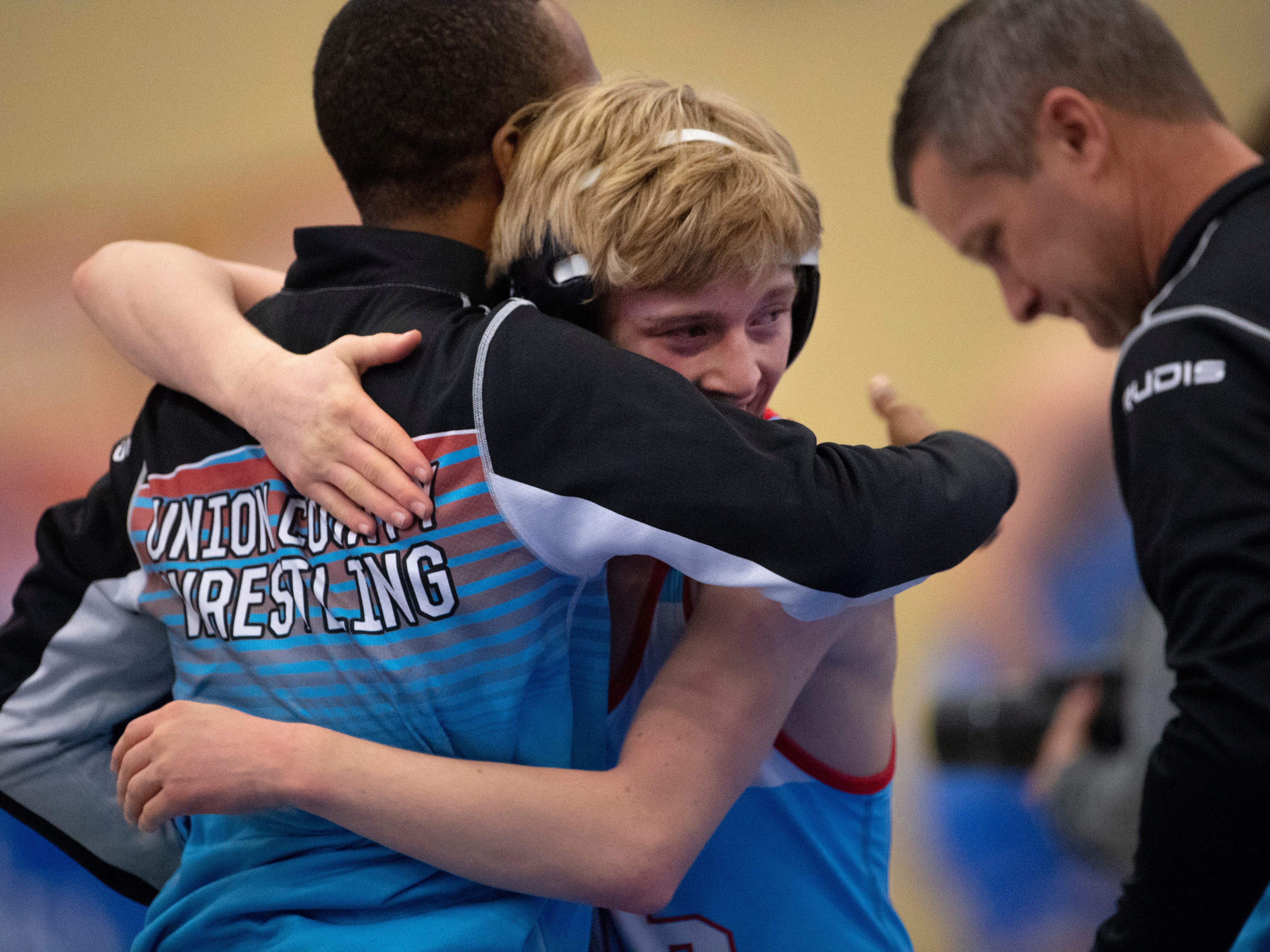 Union County's Trayce Eckman gets a hug from coach Jarvis Elam after winning his 106-pound match in his first consolation bracket match at the KHSAA State Wrestling Championships at the Alltech Arena in Lexington, Ky., Saturday afternoon. Eckman took home the third place medal for his efforts.