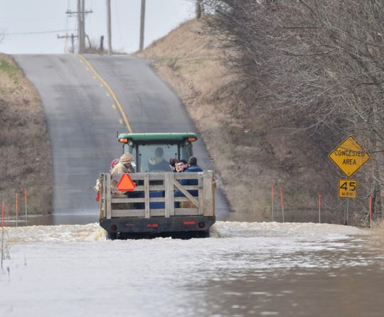 Stacey Denton, co-owner of Blue Moon Stables, ferries folks across a flooded Kentucky 268 with a tractor and wagon Saturday. The stable has to use the tractor and wagon to get riders and their families to the facility.