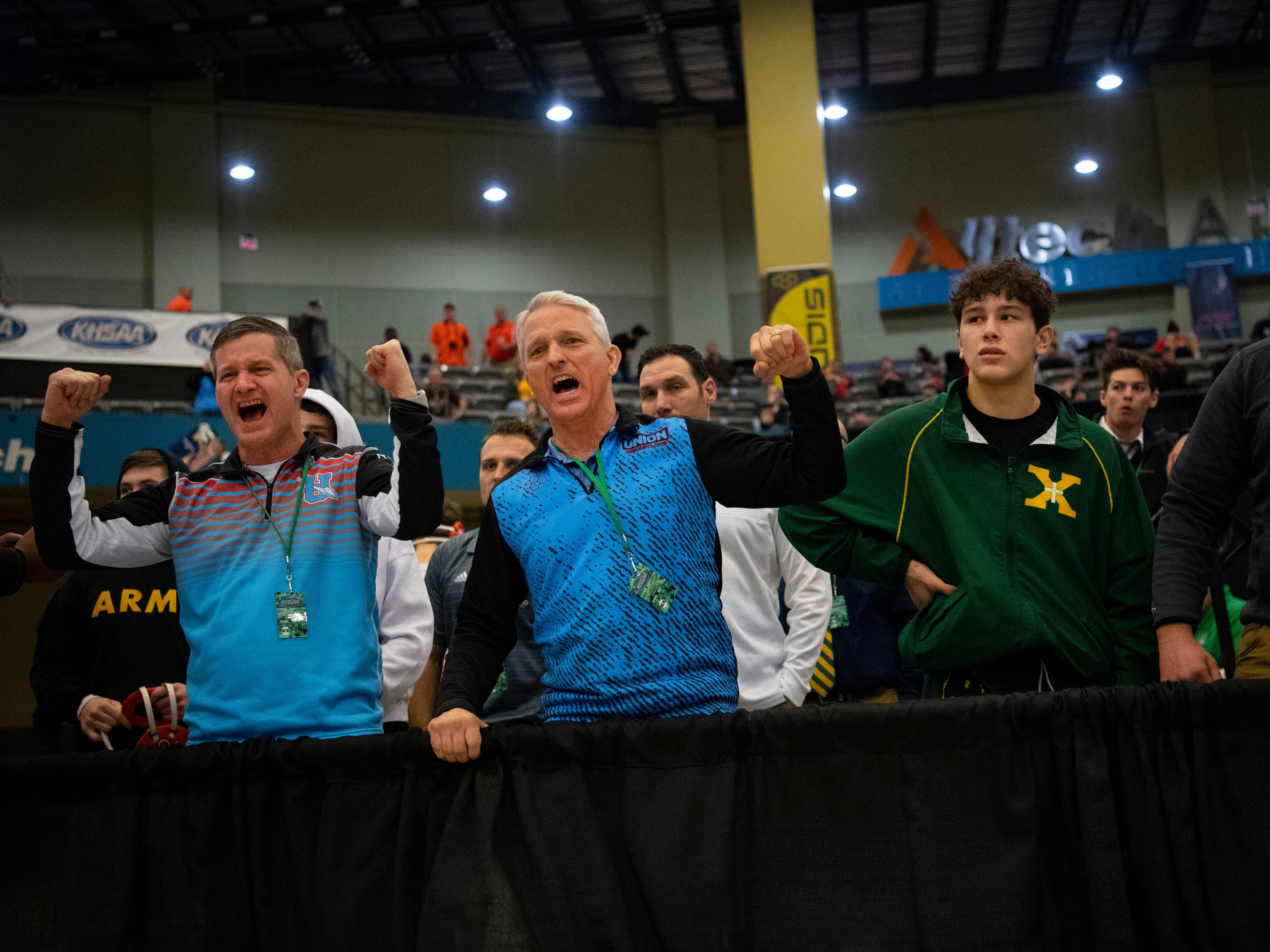 Union County coaches, from left, Brad Ervin and brother Robert Ervin, cheer on Trevor Pogue in his first consolation match in the 138 pound class at the KHSAA State Wrestling Championships at the Alltech Arena in Lexington, Ky., Saturday afternoon. Pogue finished with a fourth place award.