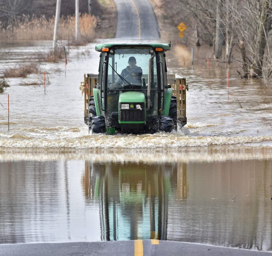 Stacy Denton fords the floodwaters of Kentucky 268 in western Henderson County as she comes to pick up equestrian students and their families.