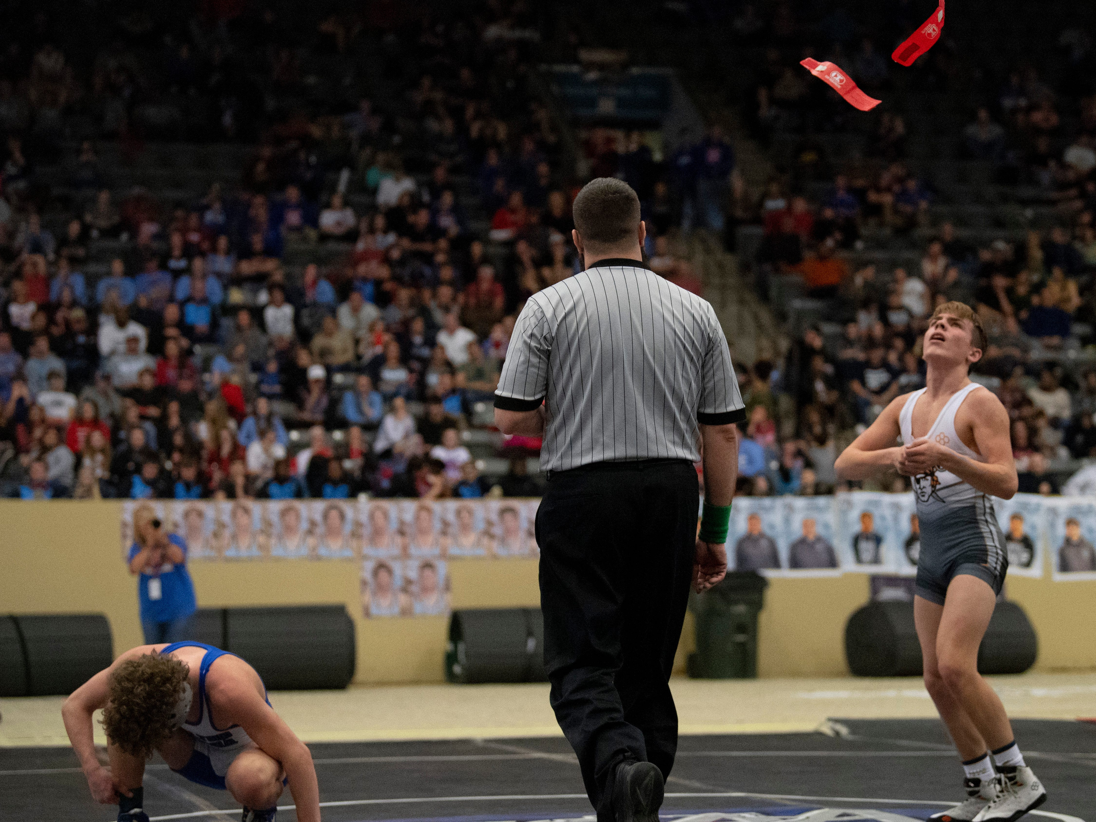Ryle's Cole Thomas tosses his anklets into the air after defeating Walton-Verona's Spencer Moore for the 106-pound championship by a tie-breaker 3-2 at the KHSAA State Wrestling Championships at the Alltech Arena in Lexington, Ky., Saturday night.