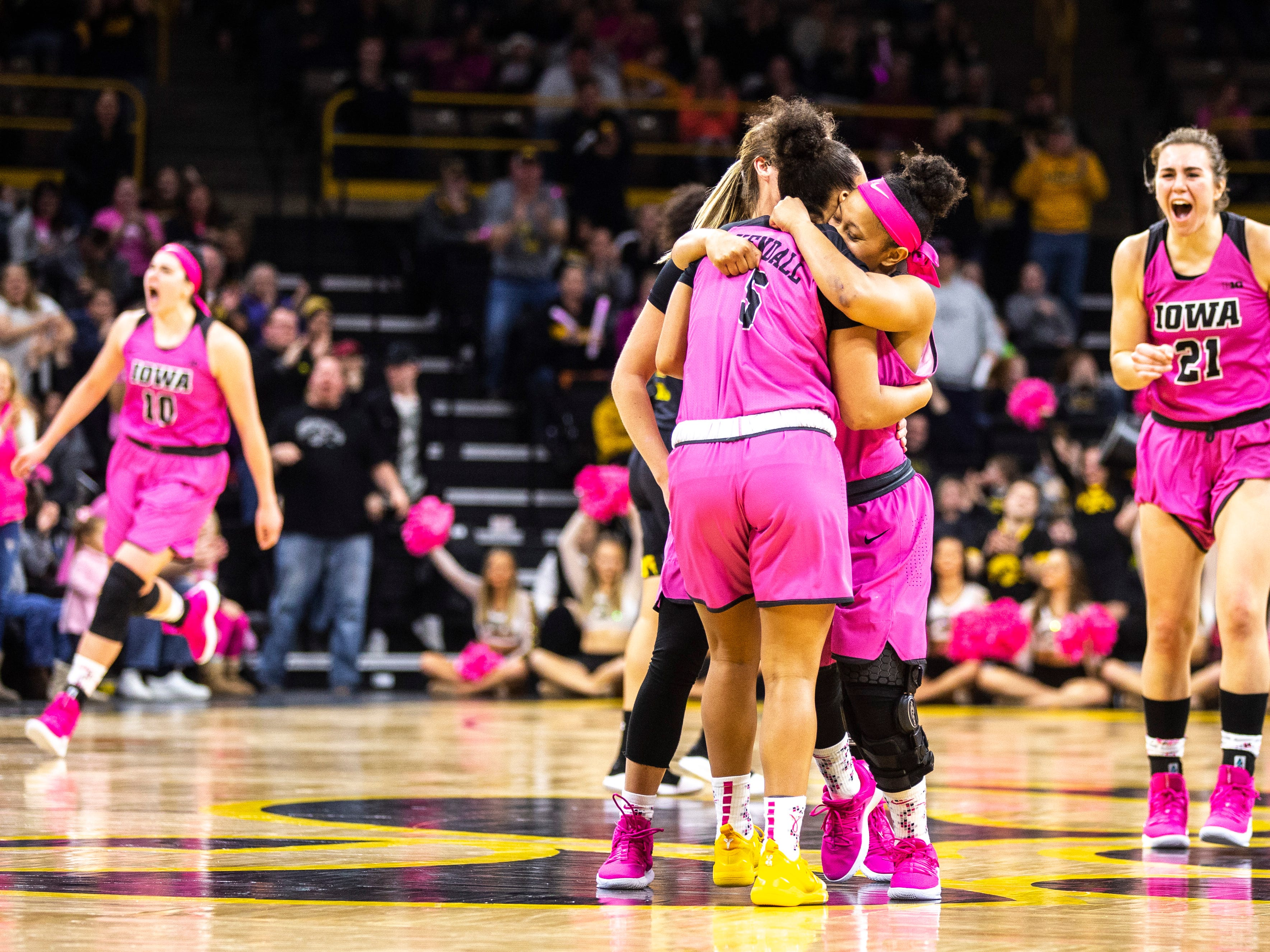 Iowa guard Alexis Sevillian (5) is embraced by guard Tania Davis after making a 3-point basket while center Megan Gustafson (10) and forward Hannah Stewart (21) celebrate in the background during a NCAA Big Ten Conference women's basketball game on Sunday, Feb. 17, 2019 at Carver-Hawkeye Arena in Iowa City, Iowa.
