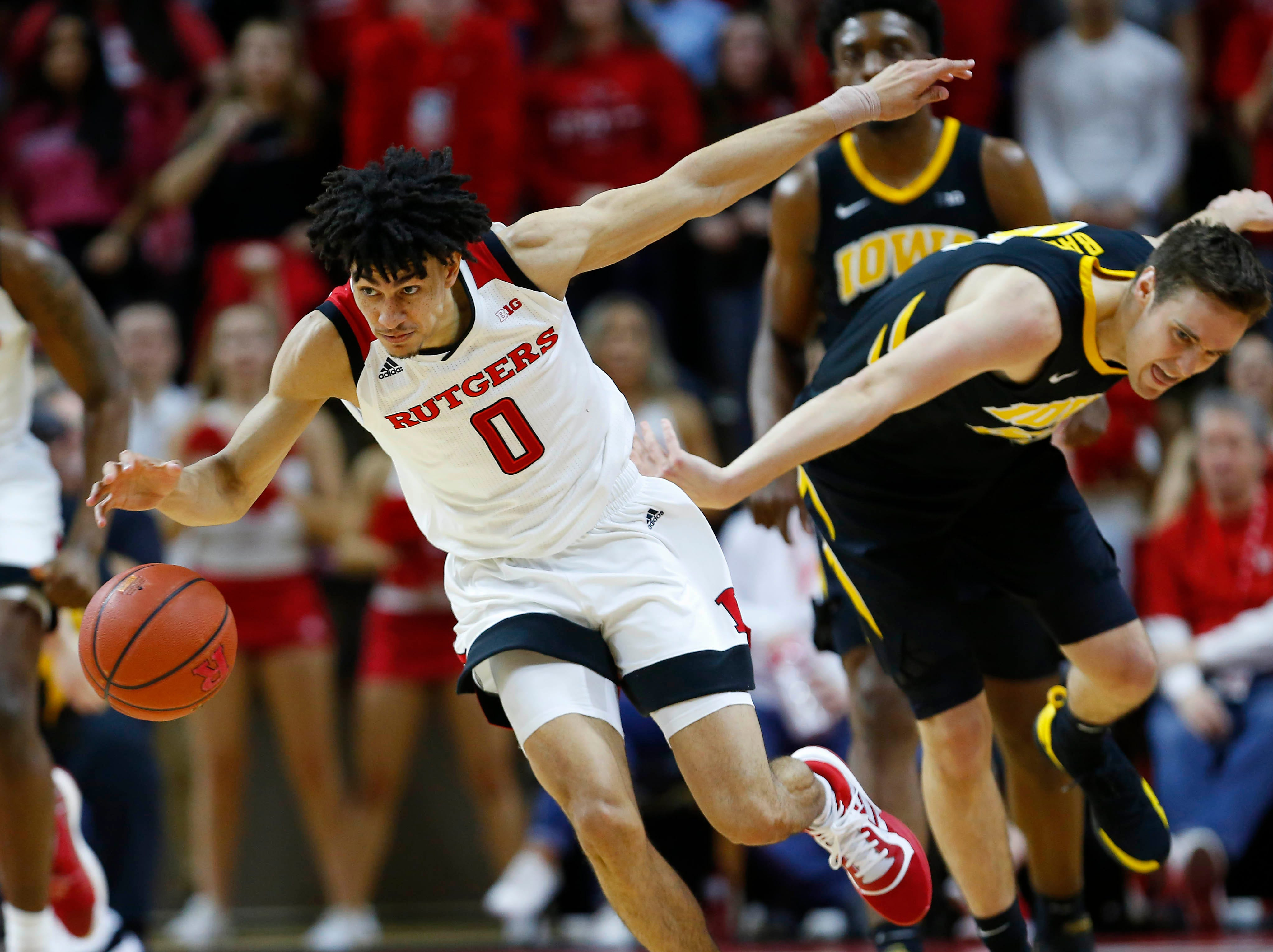 Rutgers Scarlet Knights guard Geo Baker (0) dribbles the ball against Iowa Hawkeyes forward Nicholas Baer (51) during the second half at Rutgers Athletic Center (RAC). Mandatory Credit: Noah K. Murray-USA TODAY Sports