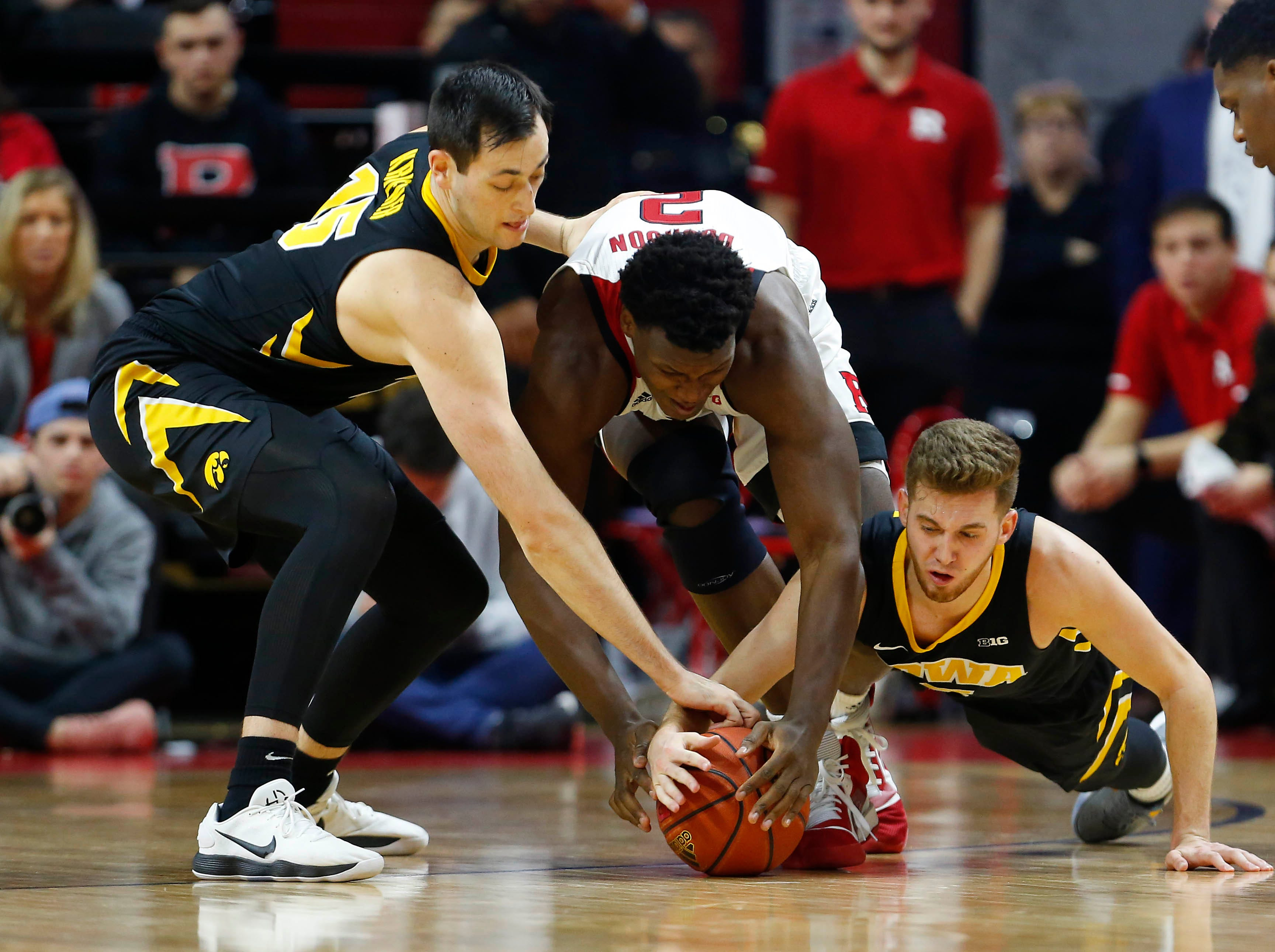 Iowa Hawkeyes forward Ryan Kriener (15) and guard Jordan Bohannon (3) battle Rutgers Scarlet Knights center Shaquille Doorson (2) for a loose ball during the second half at Rutgers Athletic Center (RAC). Mandatory Credit: Noah K. Murray-USA TODAY Sports