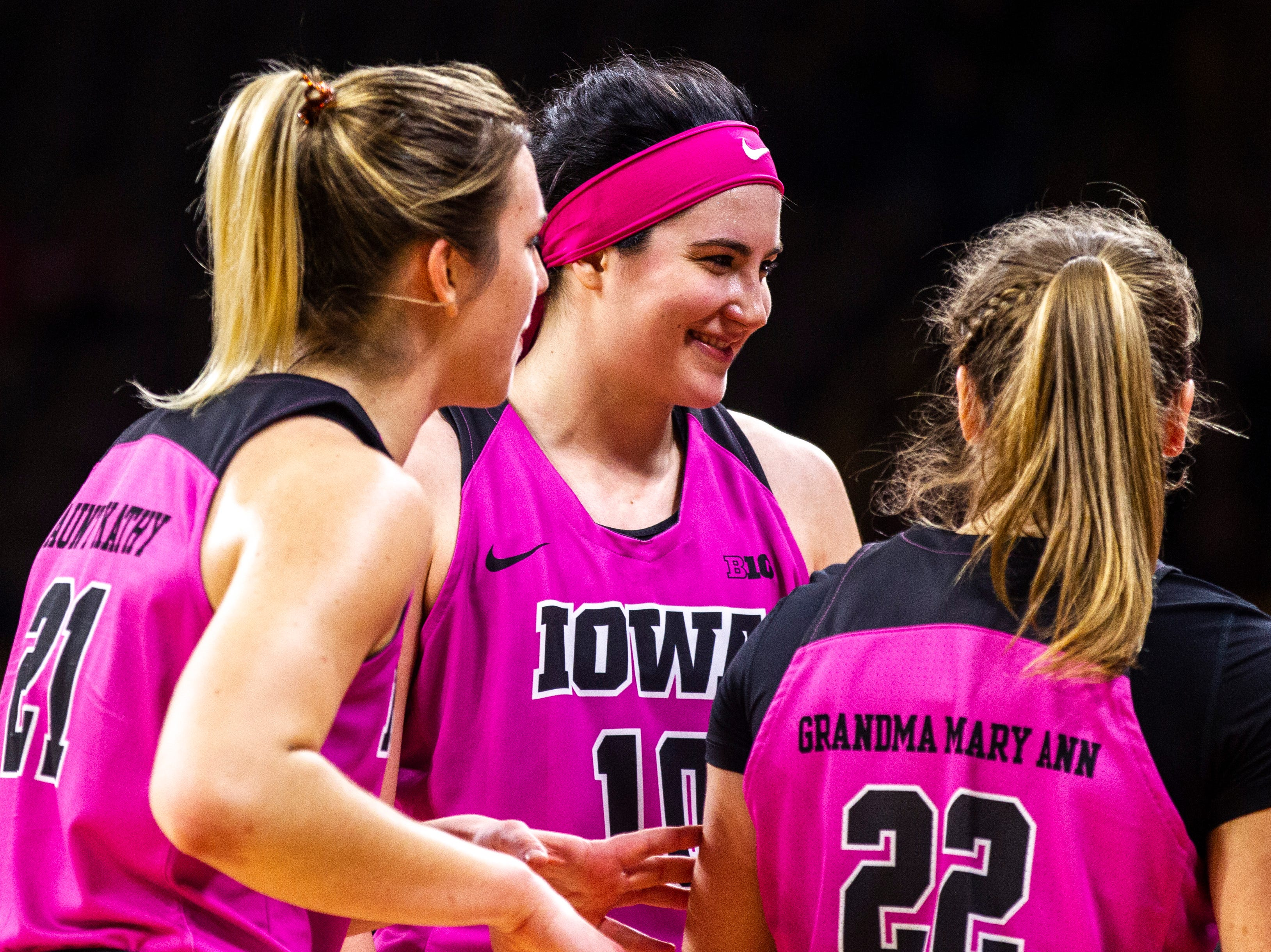 Iowa center Megan Gustafson (10) smiles while huddling with teammates Hannah Stewart (21) and Kathleen Doyle (22) during a NCAA Big Ten Conference women's basketball game on Sunday, Feb. 17, 2019 at Carver-Hawkeye Arena in Iowa City, Iowa.