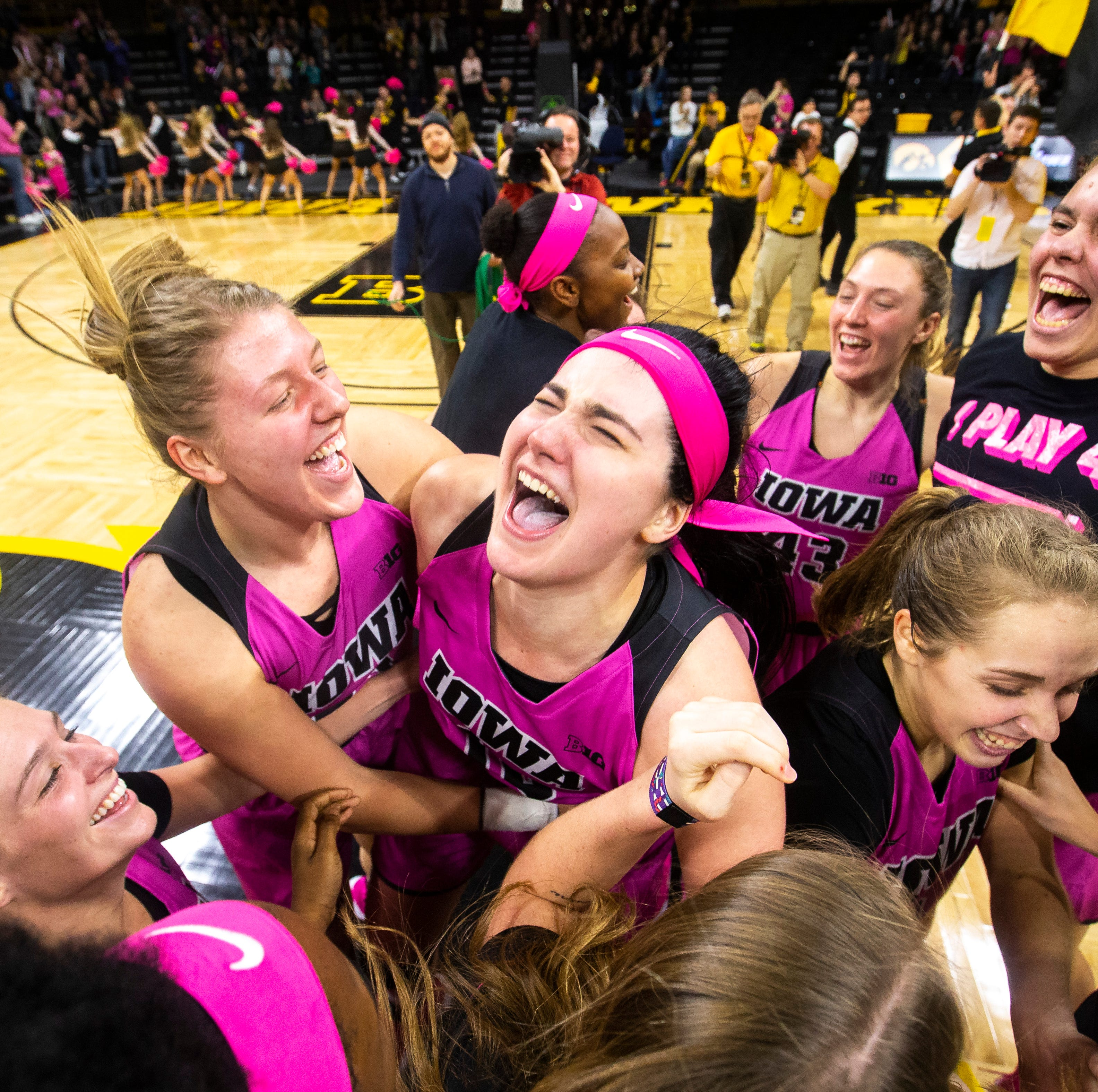 Iowa center Megan Gustafson (10) is embraced by...