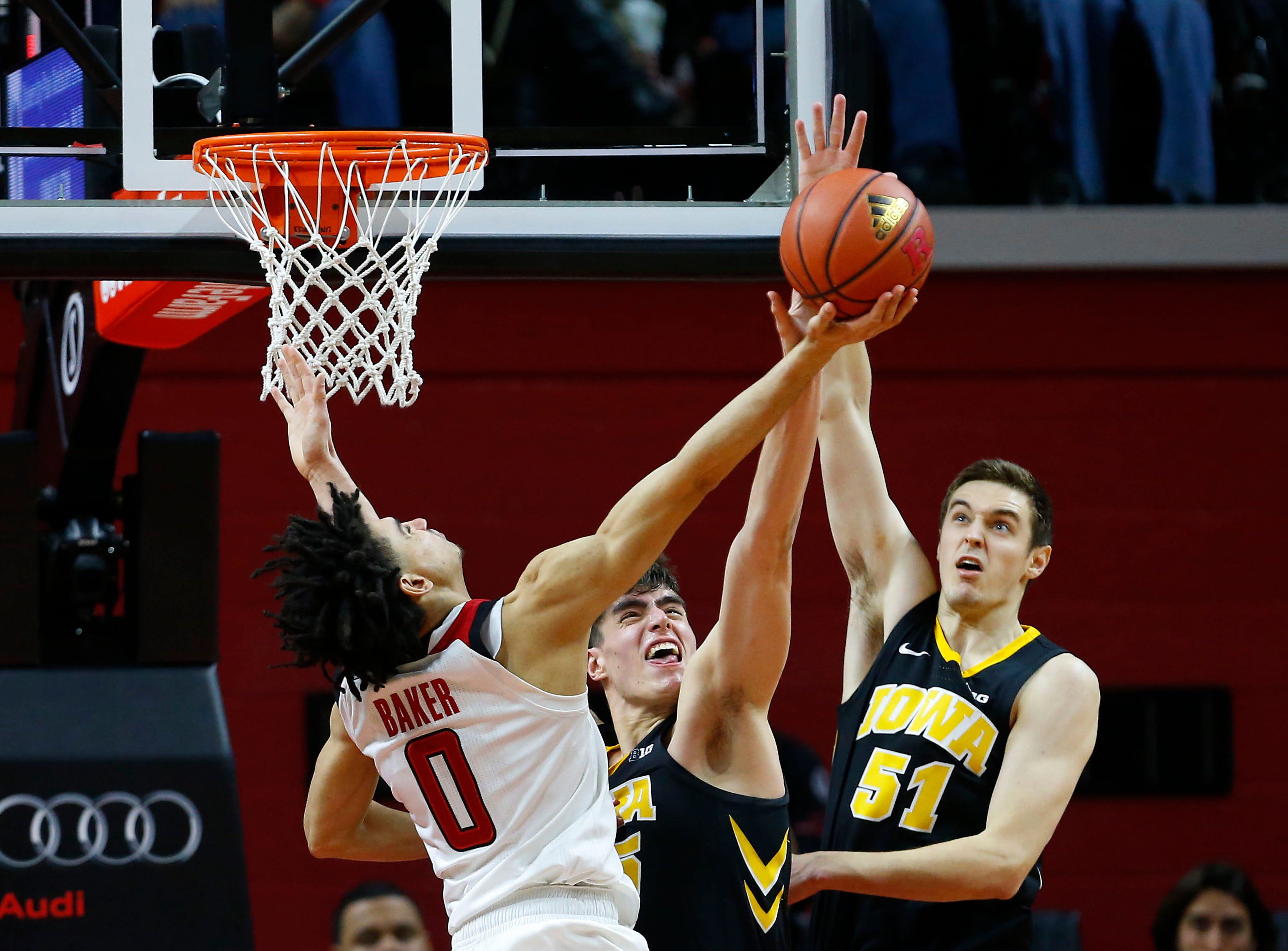 Iowa Hawkeyes forward Luka Garza (55) and Hawkeyes forward Nicholas Baer (51) defend against Rutgers Scarlet Knights guard Geo Baker (0) during the second half at Rutgers Athletic Center (RAC). Mandatory Credit: Noah K. Murray-USA TODAY Sports