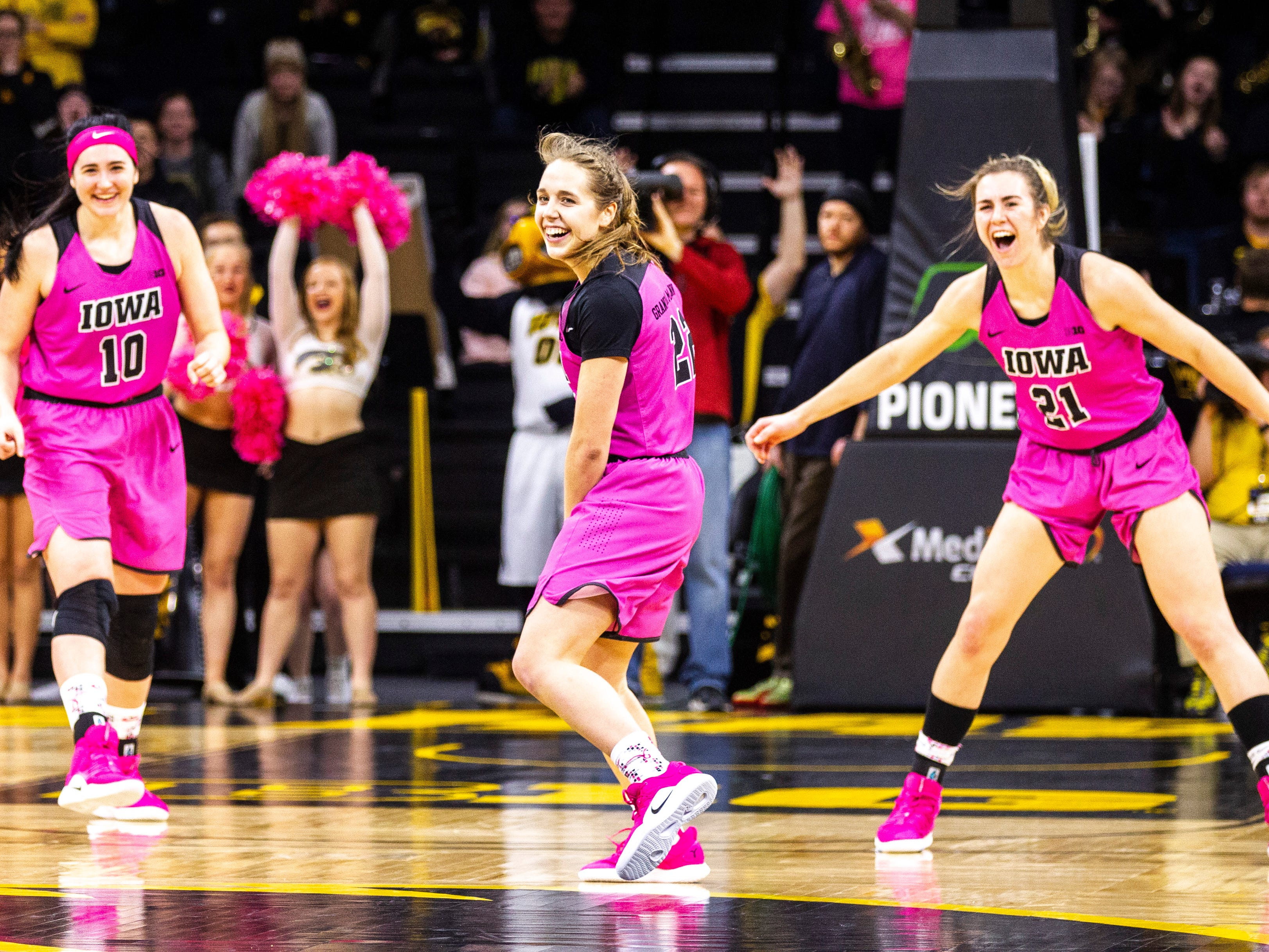 Iowa guard Kathleen Doyle (22) reacts after making a layup while Iowa center Megan Gustafson (10) and Iowa forward Hannah Stewart (21) settle in on defense during a NCAA Big Ten Conference women's basketball game on Sunday, Feb. 17, 2019 at Carver-Hawkeye Arena in Iowa City, Iowa.