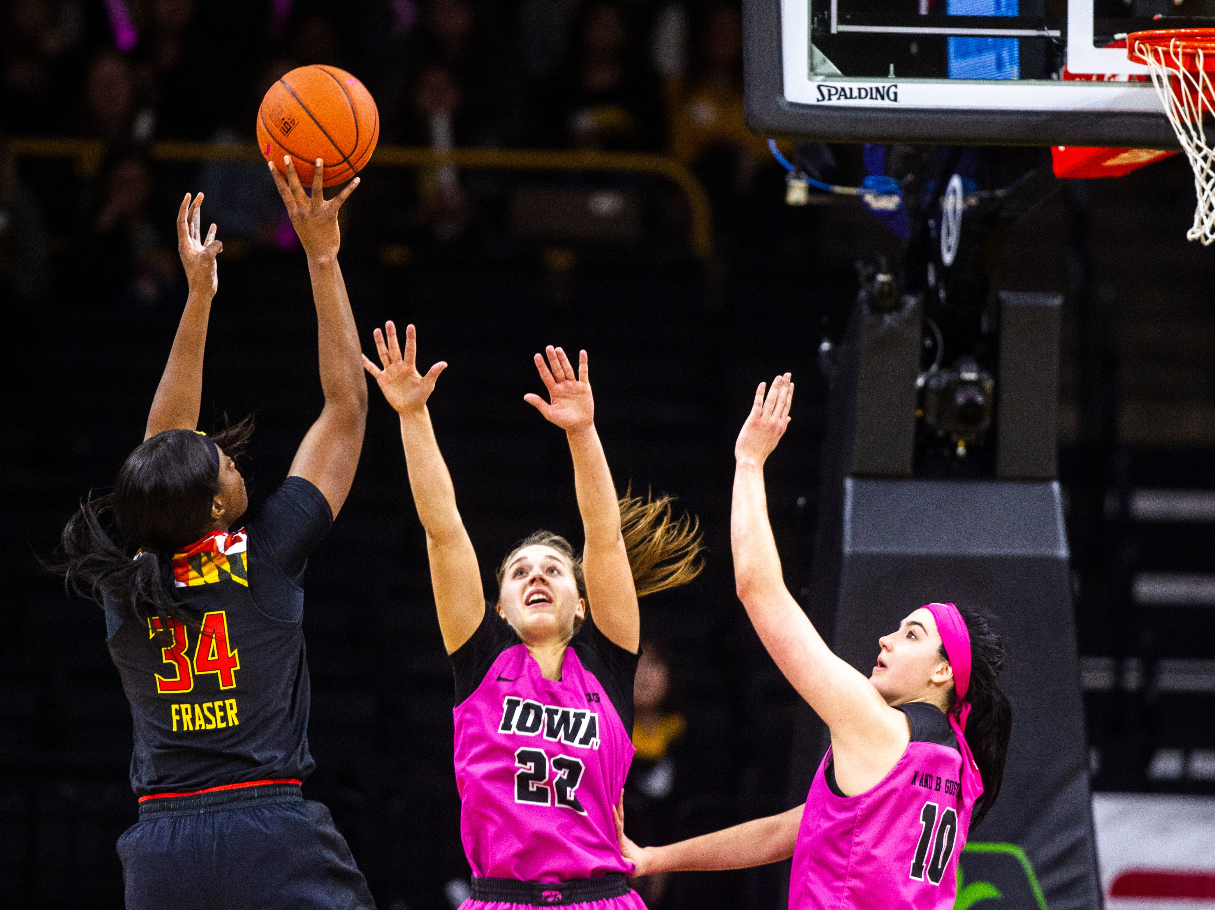 Maryland forward Brianna Fraser (34) attempts a basket while Iowa guard Kathleen Doyle (22) and Iowa center Megan Gustafson (10) defend during a NCAA Big Ten Conference women's basketball game on Sunday, Feb. 17, 2019 at Carver-Hawkeye Arena in Iowa City, Iowa.
