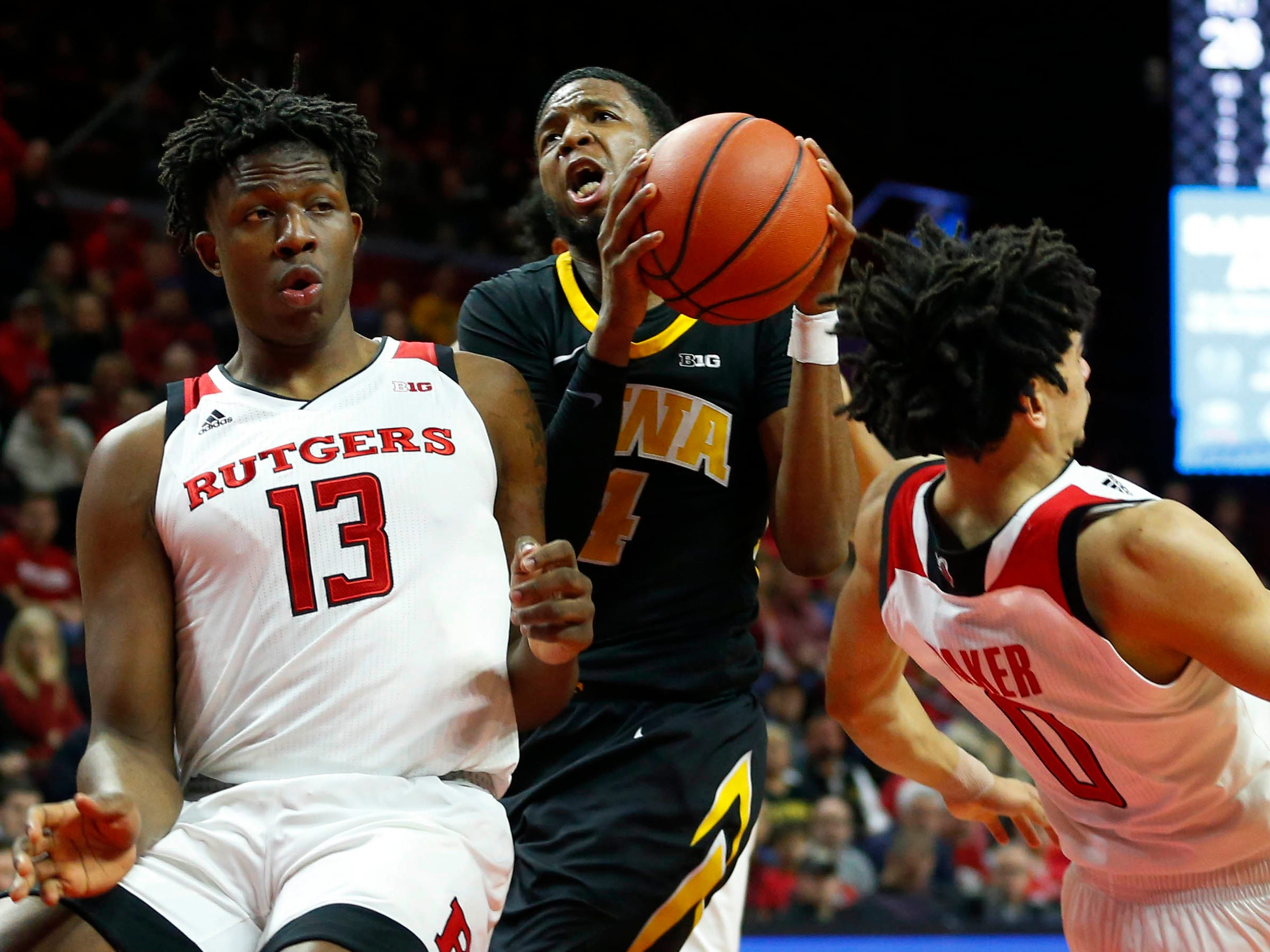 Rutgers Scarlet Knights forward Shaq Carter (13) defends with guard Geo Baker (0) who is called for a foul against Iowa Hawkeyes guard Isaiah Moss (4) during the first half at Rutgers Athletic Center (RAC). Mandatory Credit: Noah K. Murray-USA TODAY Sports