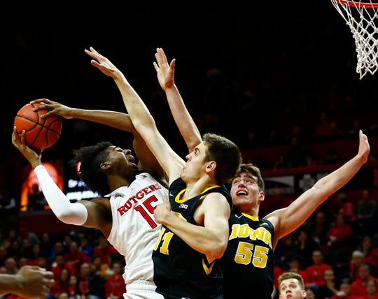Iowa's Nicholas Baer (left) and Luka Garza swallow up Rutgers center Myles Johnson on Saturday at the RAC. The No. 17 Hawkeyes didn't flinch vs. the physical Scarlet Knights this year, earning a 71-69 victory,