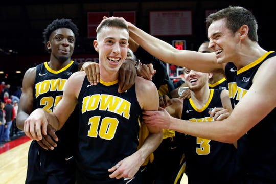 Iowa forward Joe Wieskamp (10) celebrates with teammates Tyler Cook, (from left), Jordan Bohannon and Nicholas Baer after his game-winning 3-pointer against Rutgers on Saturday.