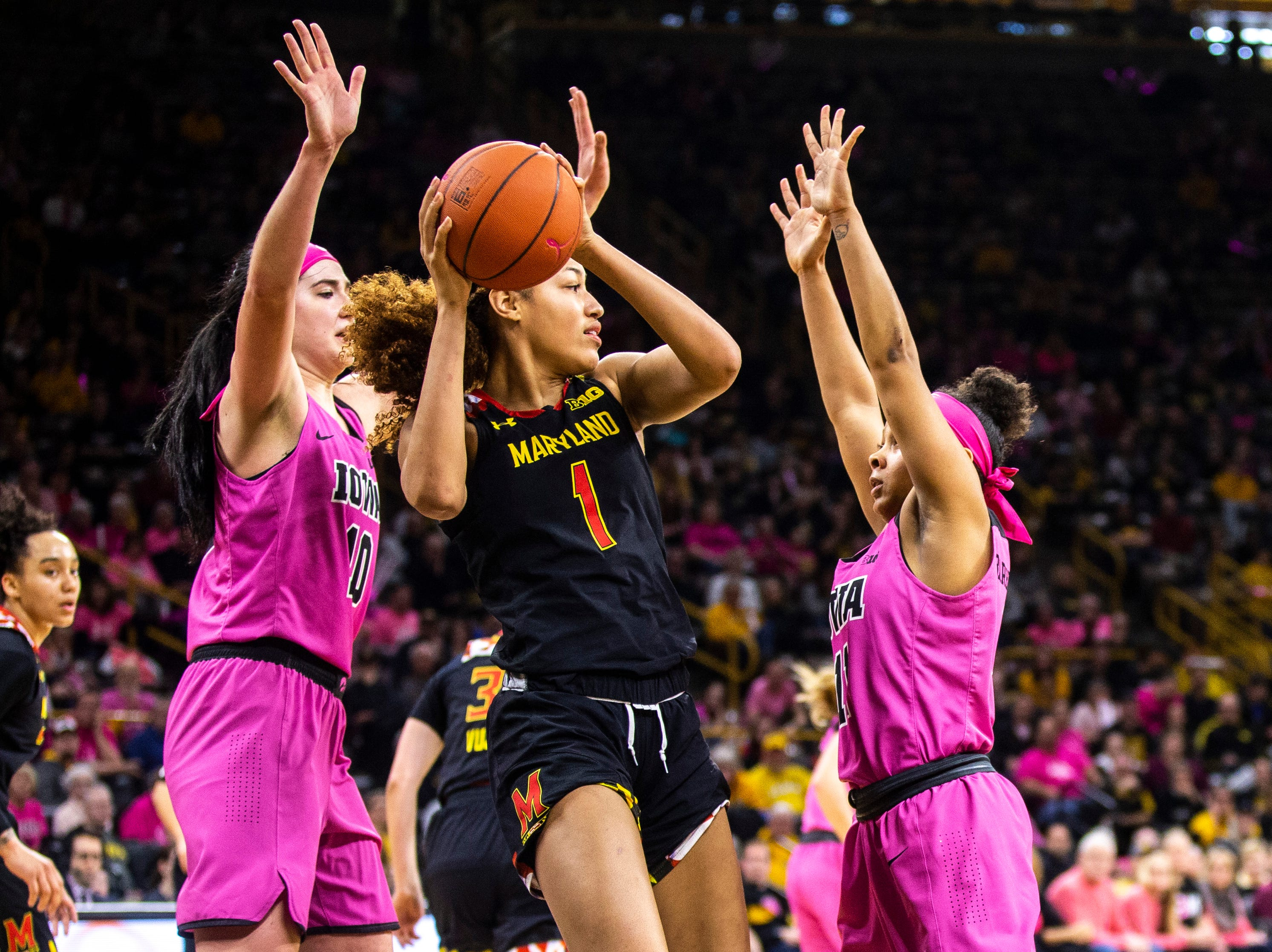 Maryland forward Shakira Austin (1) looks to pass after pulling down a rebound while Iowa center Megan Gustafson (10) and Iowa guard Tania Davis, right, defend during a NCAA Big Ten Conference women's basketball game on Sunday, Feb. 17, 2019 at Carver-Hawkeye Arena in Iowa City, Iowa.
