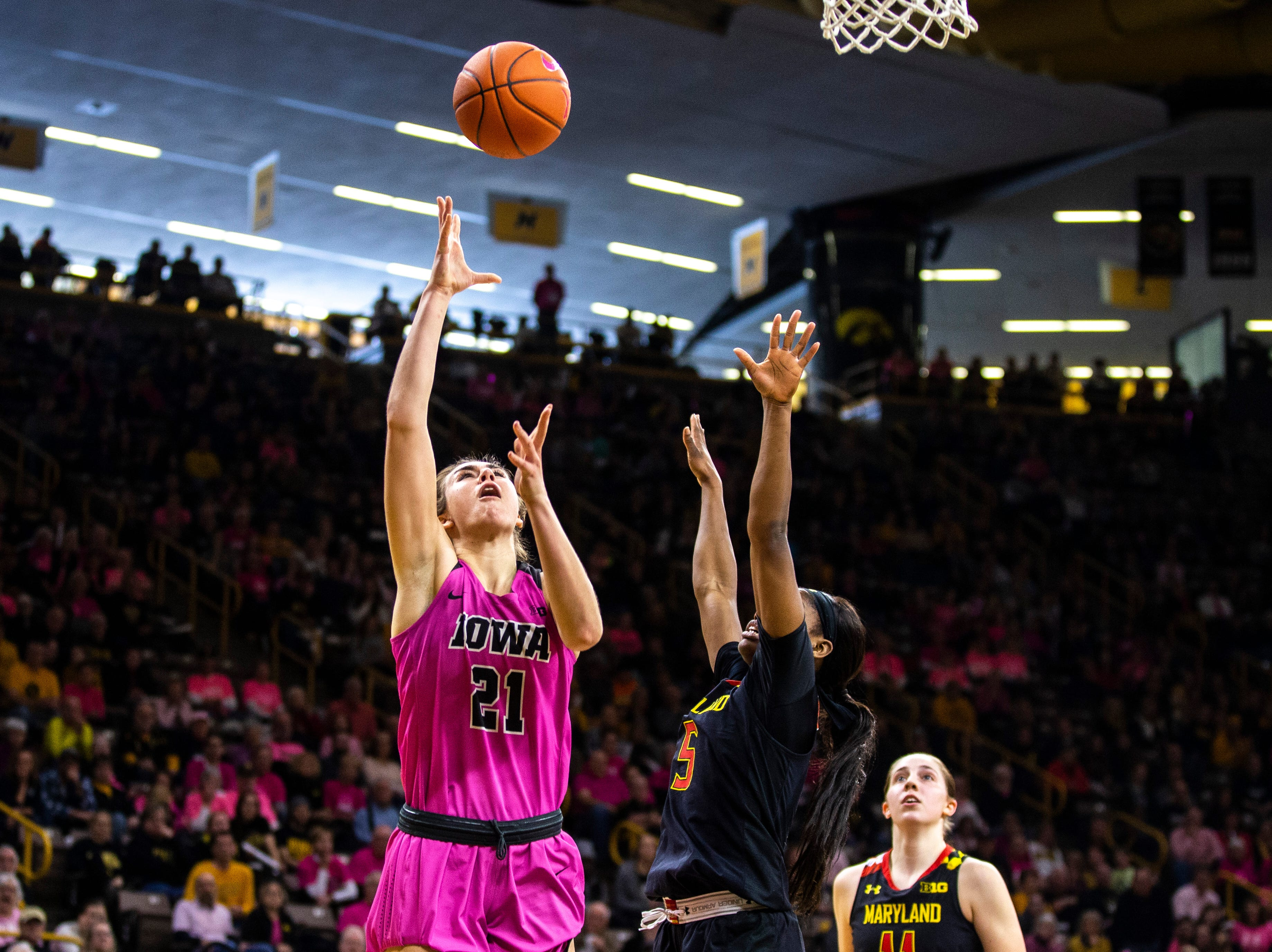 Iowa forward Hannah Stewart (21) makes a layup while Maryland guard Kaila Charles (5) defends during a NCAA Big Ten Conference women's basketball game on Sunday, Feb. 17, 2019 at Carver-Hawkeye Arena in Iowa City, Iowa.