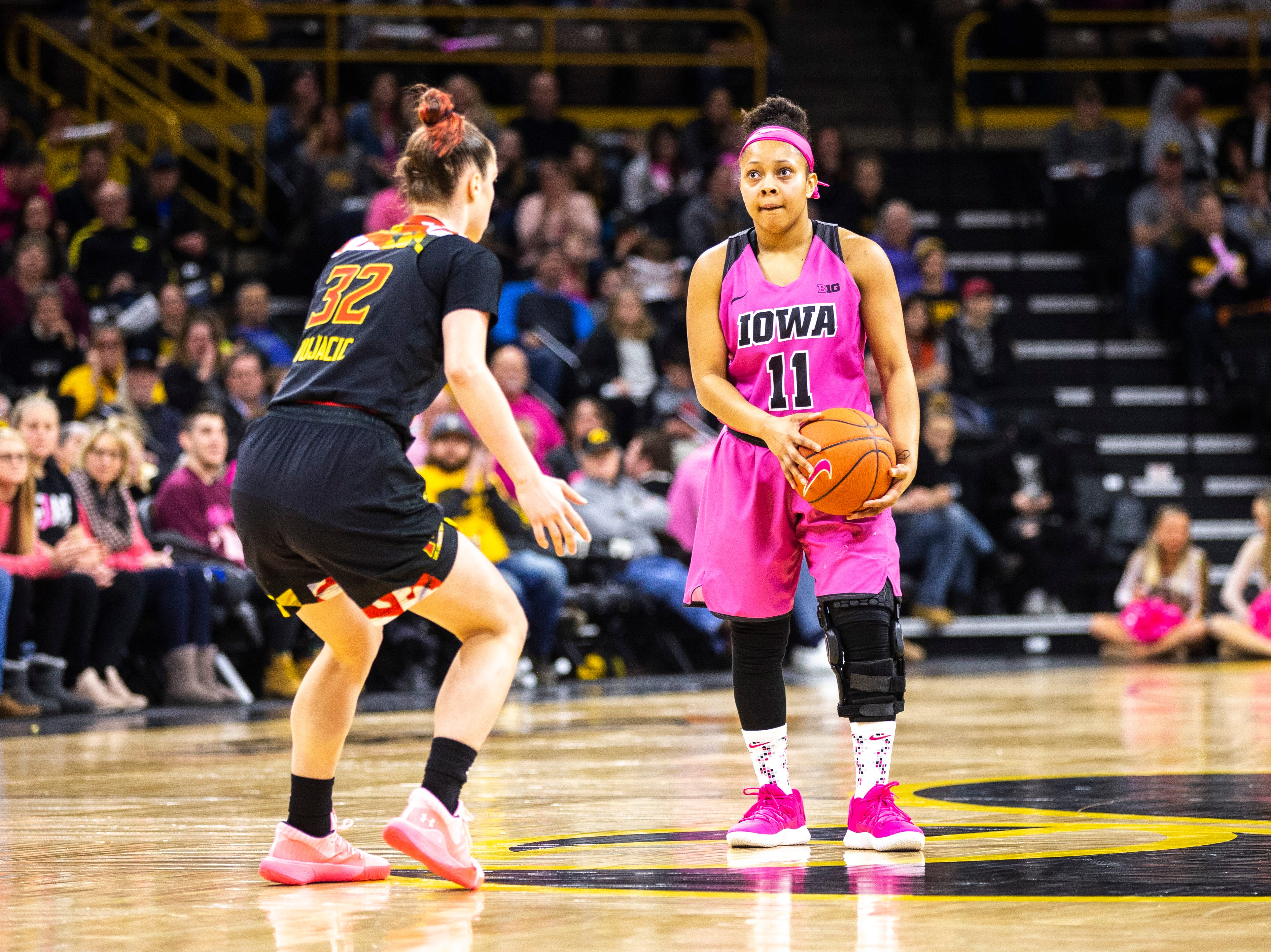 Iowa guard Tania Davis (11) watches the shot clock wind down while Maryland guard Sara Vujacic (32) defends during a NCAA Big Ten Conference women's basketball game on Sunday, Feb. 17, 2019 at Carver-Hawkeye Arena in Iowa City, Iowa.