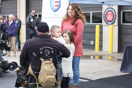 """Dameon Berry, his wife, Jamie, and children, 3-year-old Isaac and 6-year-old Kendall, wait for the official presentation of the all-terrain wheelchair. """"It's made him so much happier,"""" said Jamie Berry."""