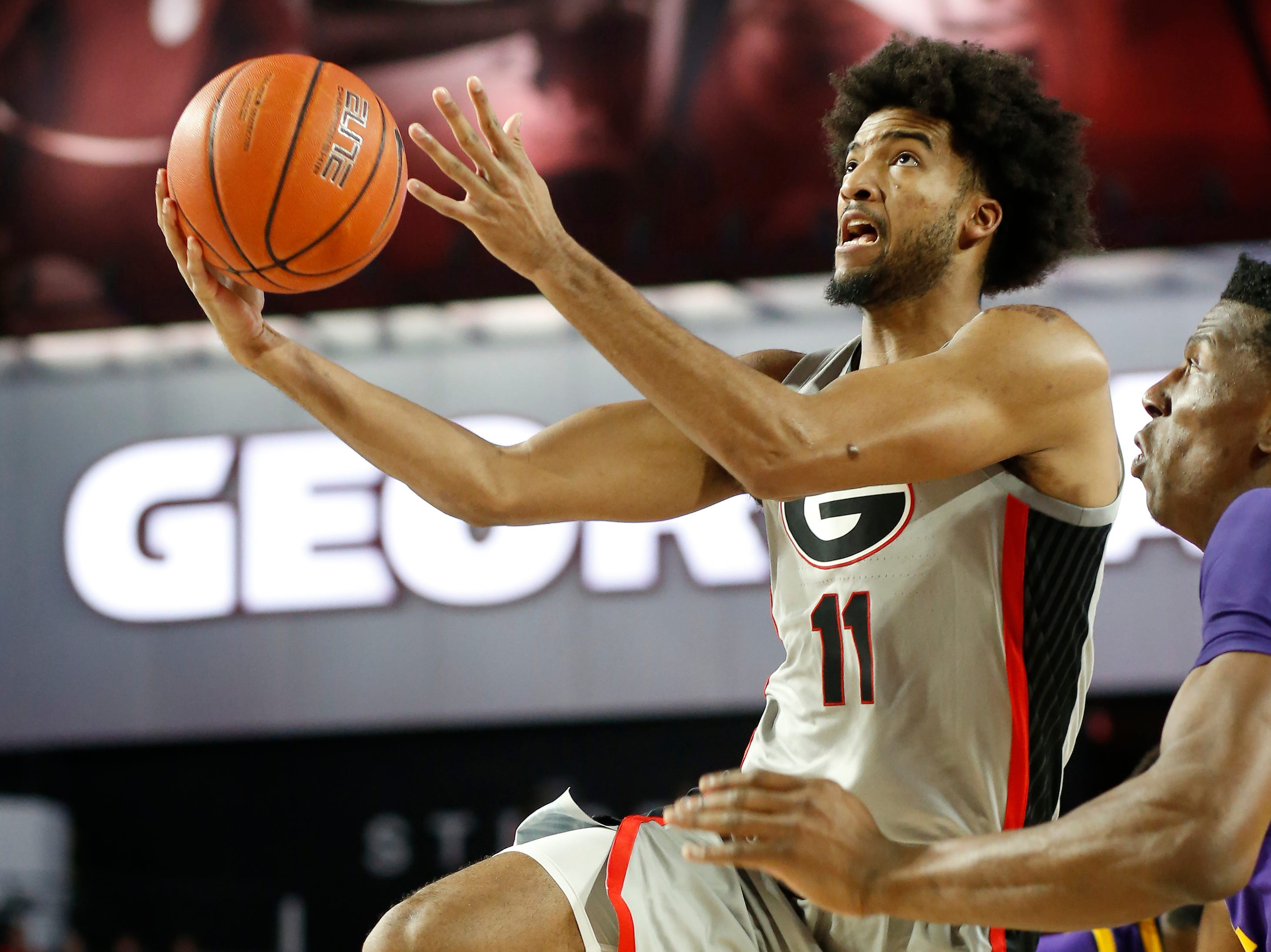 Georgia guard Christian Harrison (11) takes a shot past LSU forward Kavell Bigby-Williams (11) during an NCAA college basketball game in Athens, Ga., on Saturday, Feb. 16, 2019. (Joshua L. Jones/Athens Banner-Herald via AP)