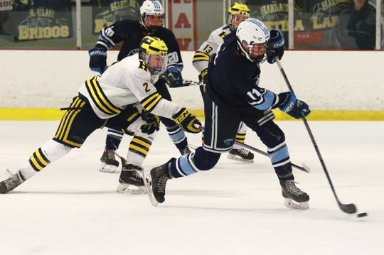 Jaydon Spears scores Livonia Stevenson's second goal while defended by Kieran Carlile (2) in a 5-2 victory over Hartland on Saturday, Feb. 16, 2019.