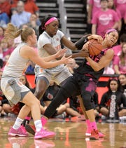 Louisville guard Asia Durr (25) battles Miami forward Khalia Prather (25), center, and guard Laura Cornelius (1) for the ball during the first half of an NCAA college basketball game in Louisville on Sunday, Feb. 17, 2019.)