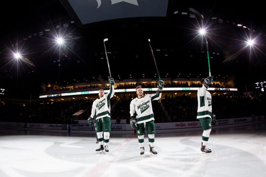 Michigan State hockey seniors Cody Milan (left), Zach Osburn (center) and Brennan Sanford (right) raise their sticks to the crowd at Munn Ice Arena. The three seniors likely played their last home game of their collegiate careers on Saturday.