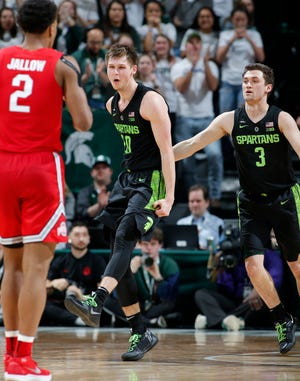 Michigan State's Matt McQuaid, center, and Foster Loyer, right, and Ohio State's Musa Jallow (2) react during the second half of an NCAA college basketball game, Sunday, Feb. 17, 2019, in East Lansing, Mich. (AP Photo/Al Goldis)