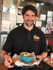 Las Tortugas Deli Mexicana owner Jonathan Magallanes delivers a bowl of tortilla soup to a table.