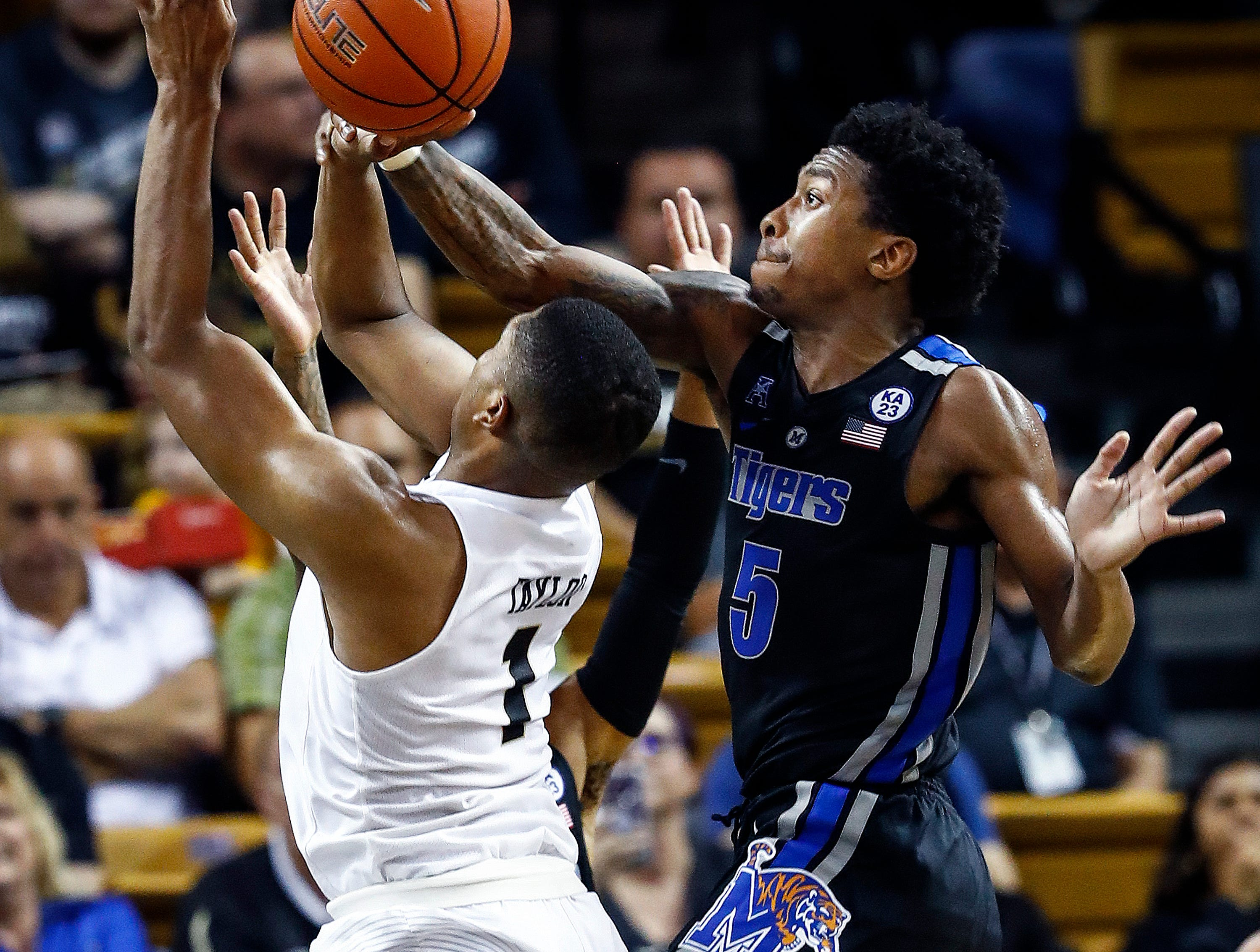 Memphis defender Kareem Brewton Jr. (right) is called for a foul while blocking the shot of UCF guard BJ Taylor (left) during action in Orlando Saturday, February 16, 2019.