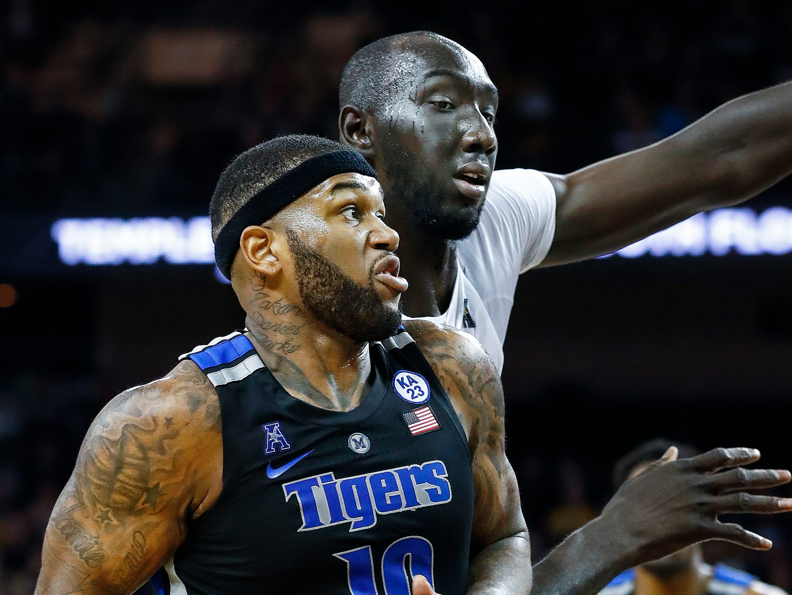 Memphis forward Mike Parks Jr. (left) drives the lane against UCF defender Tacko Fall (right) during action in Orlando Saturday, February 16, 2019.