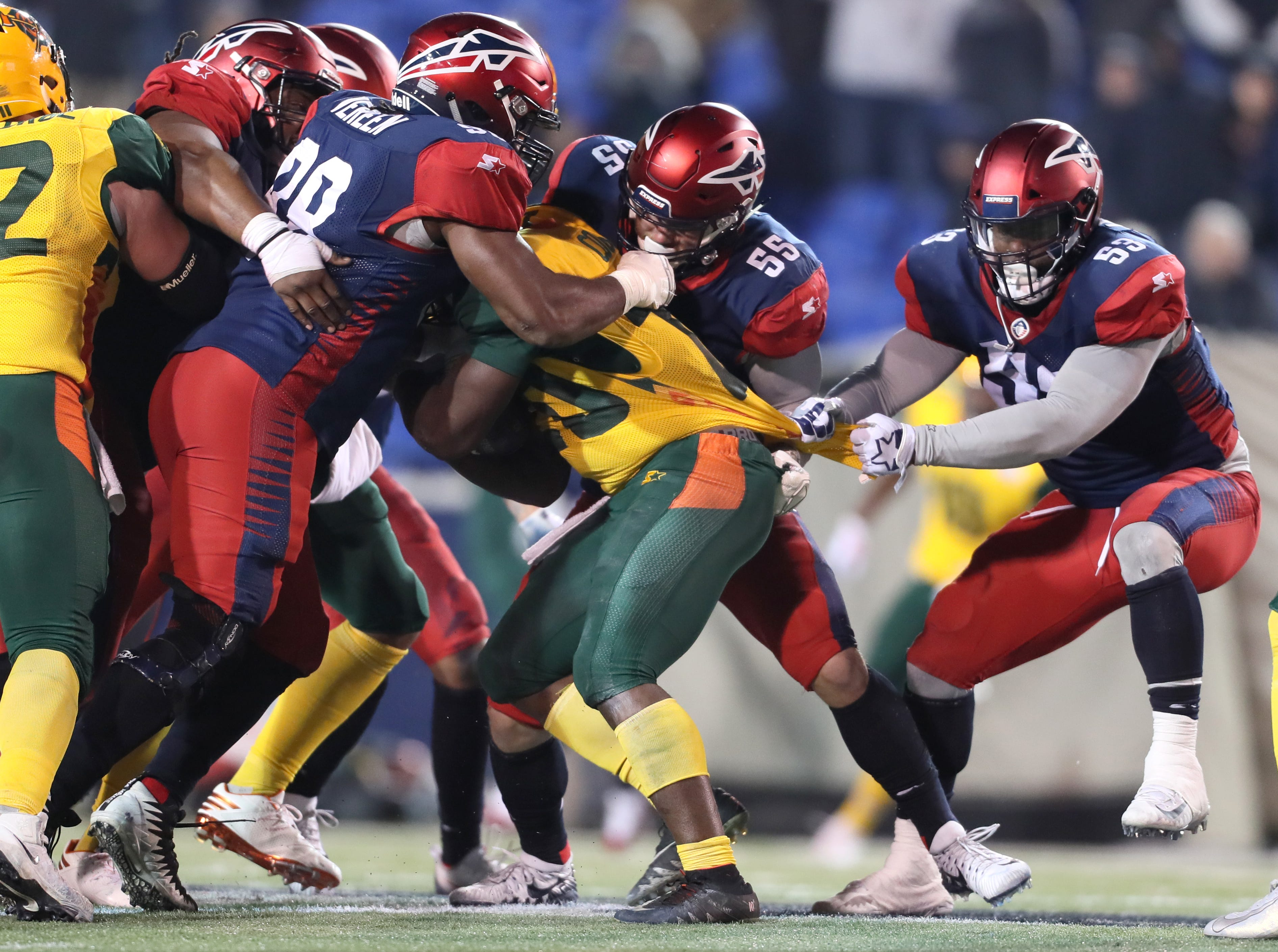 Memphis Express defensive players Corey Vereen, from left, Davis Tull and Drew Jackson pull down Arizona Hotshots running back Tim Cook during their game at the Liberty Bowl on Saturday, Feb. 16, 2019.