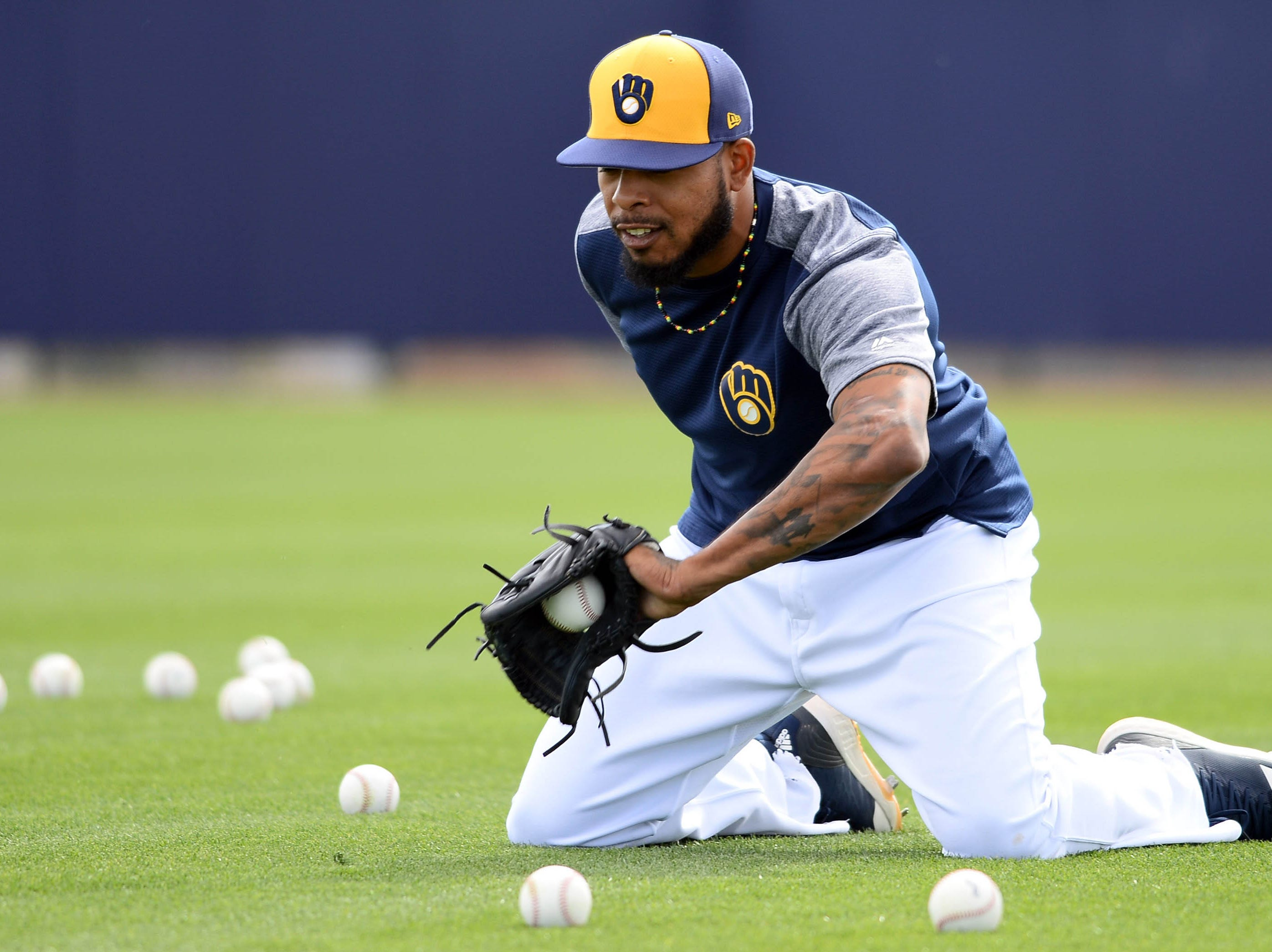 Reliever Jeremy Jeffress fields a ball while kneeling Saturday.