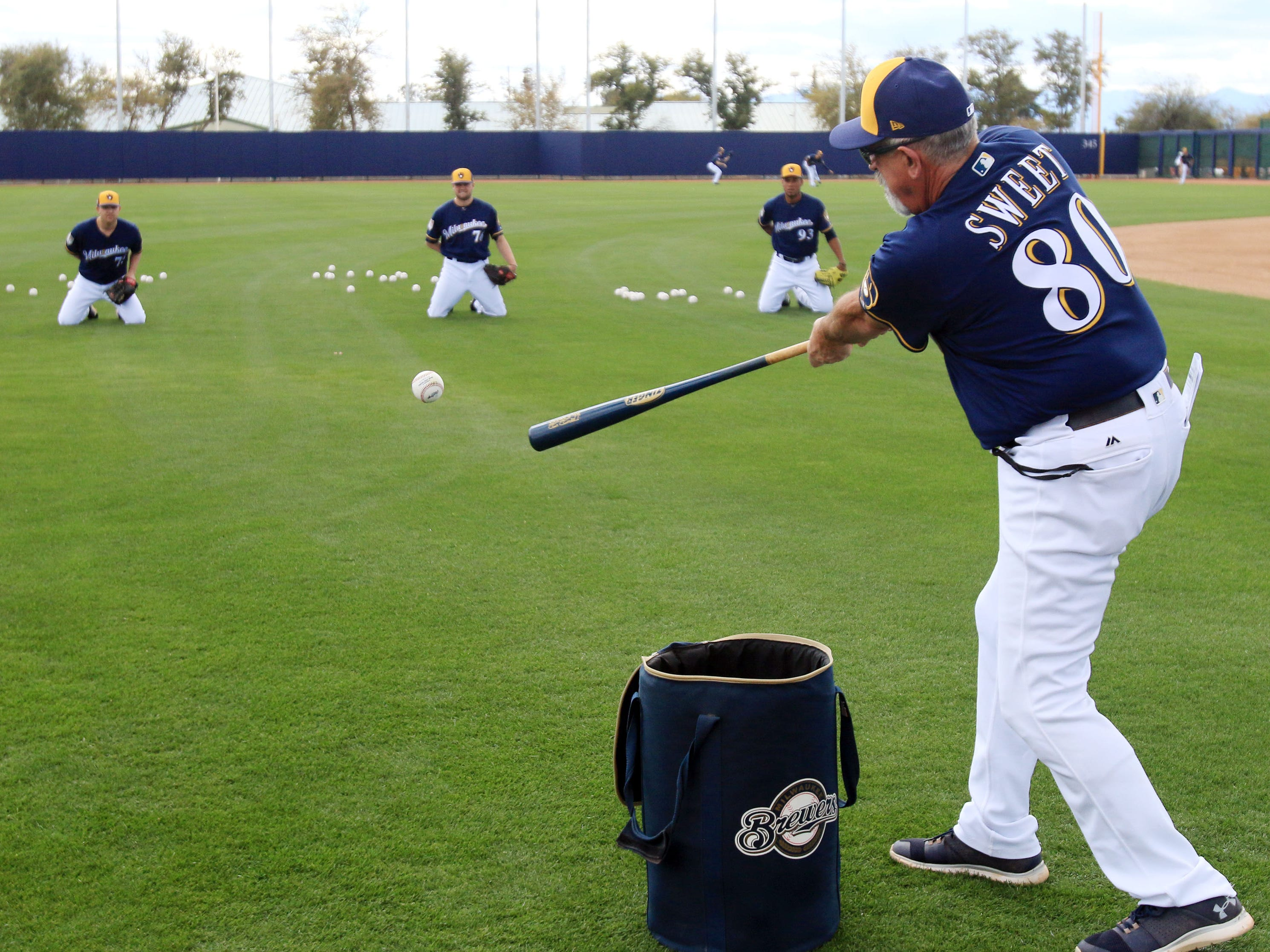 Brewers instructor Rick Sweet hits grounds at kneeling pitchers during practice on Saturday.