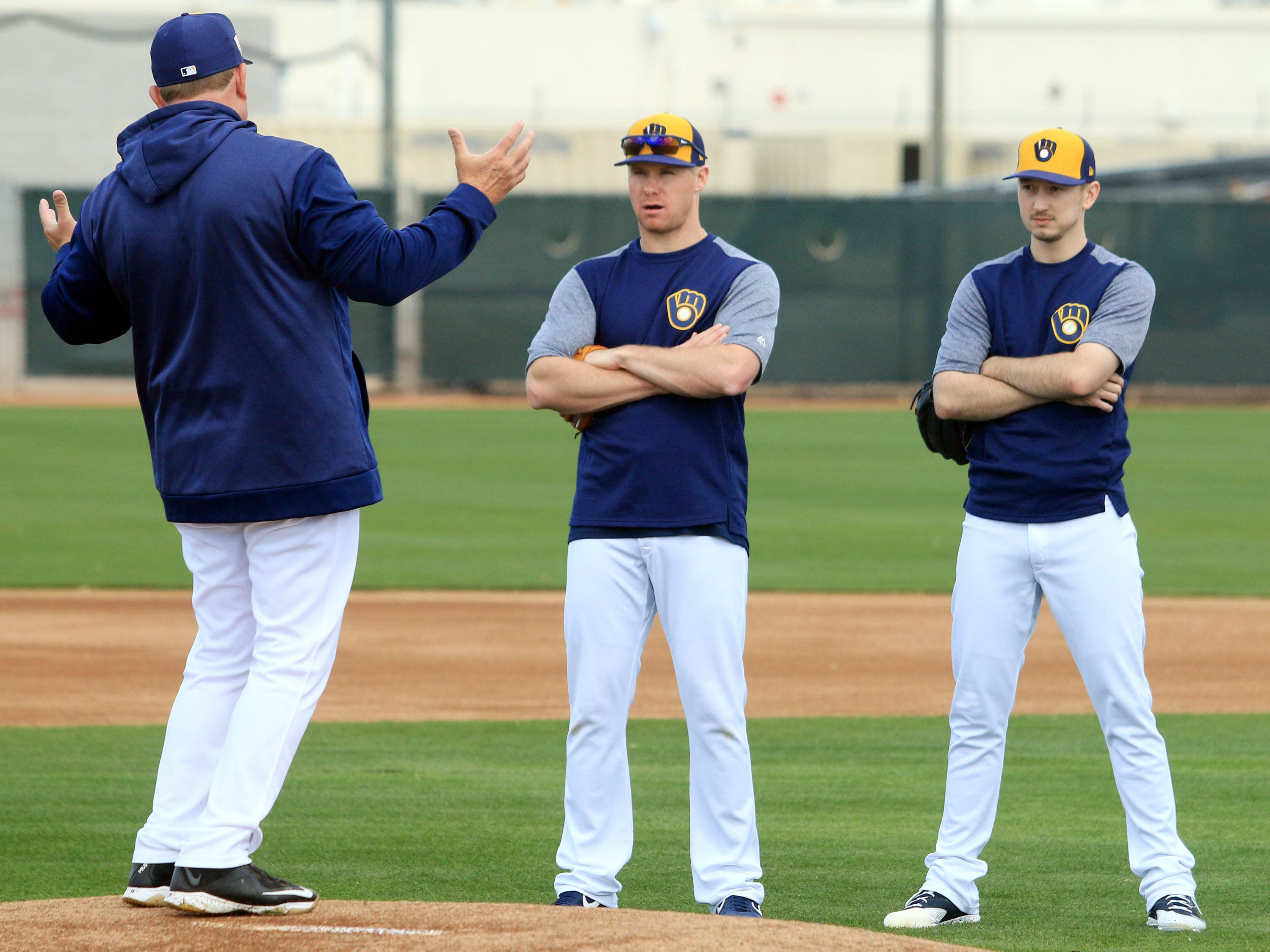 Brewers bench coach Pat Murphy, left, has the attention of pitchers Chase Anderson and Zach Davies on Saturday.