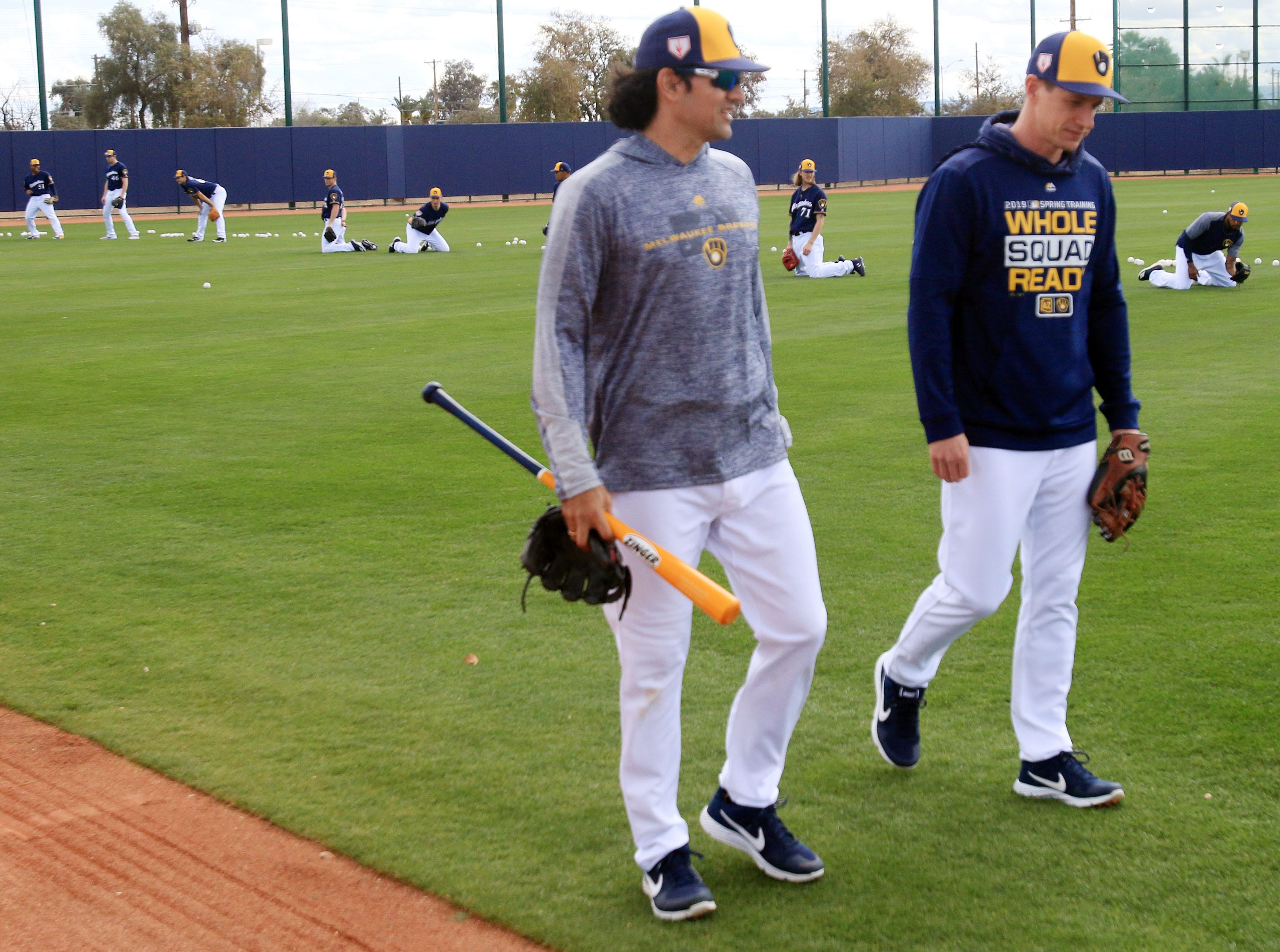 Brewers manager Craig Counsell (right) and first base coach Carlos Subero head to their next drill Saturday.