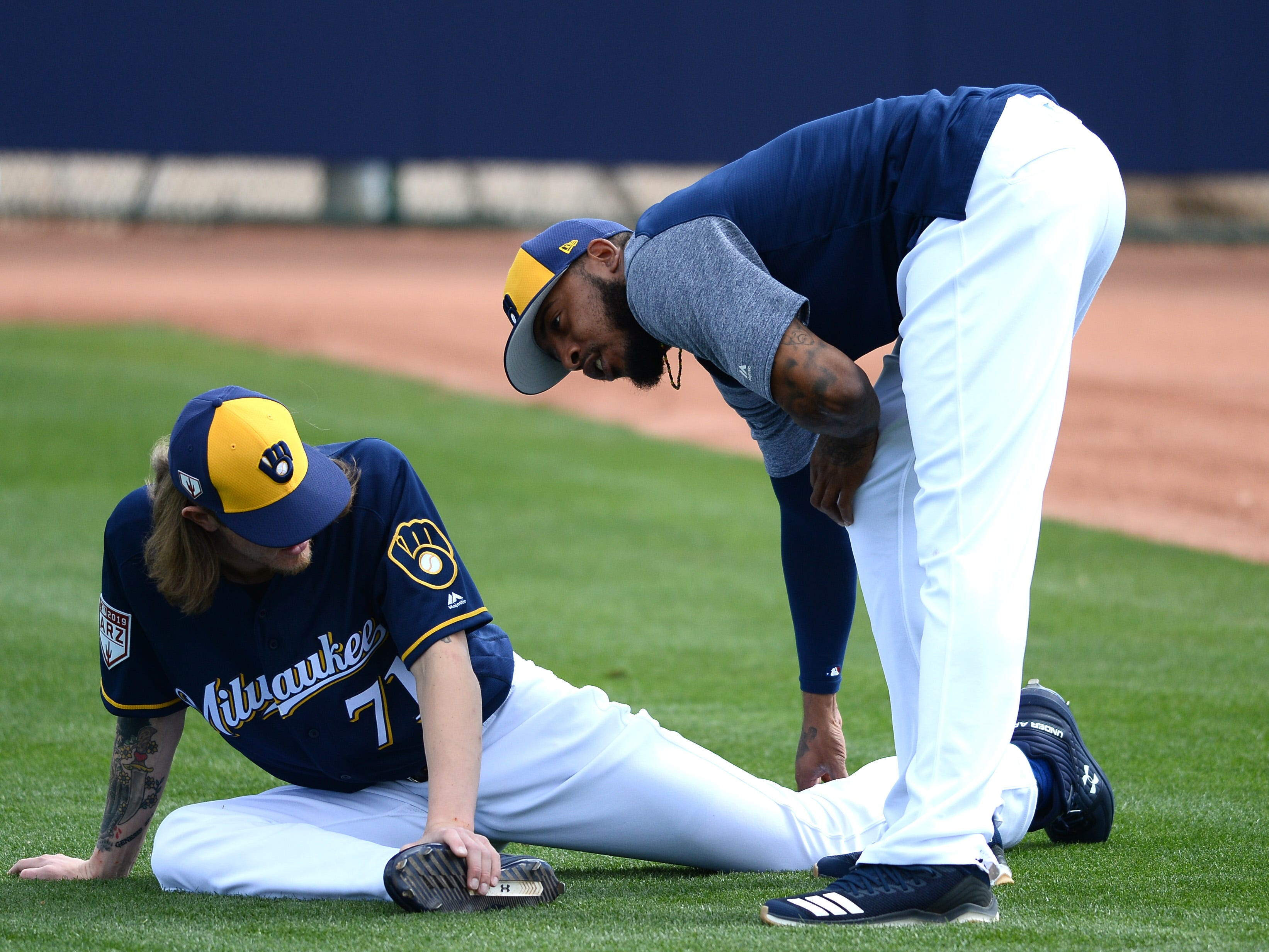 Josh Hader (left) talks with fellow reliever Jeremy Jeffress as he stretches for practice Saturday.