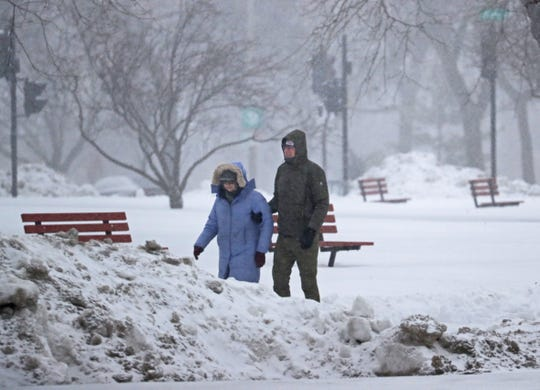 New-fallen snow makes for slippery walking as this couple makes their way along East Kilbourn Avenue on Sunday.