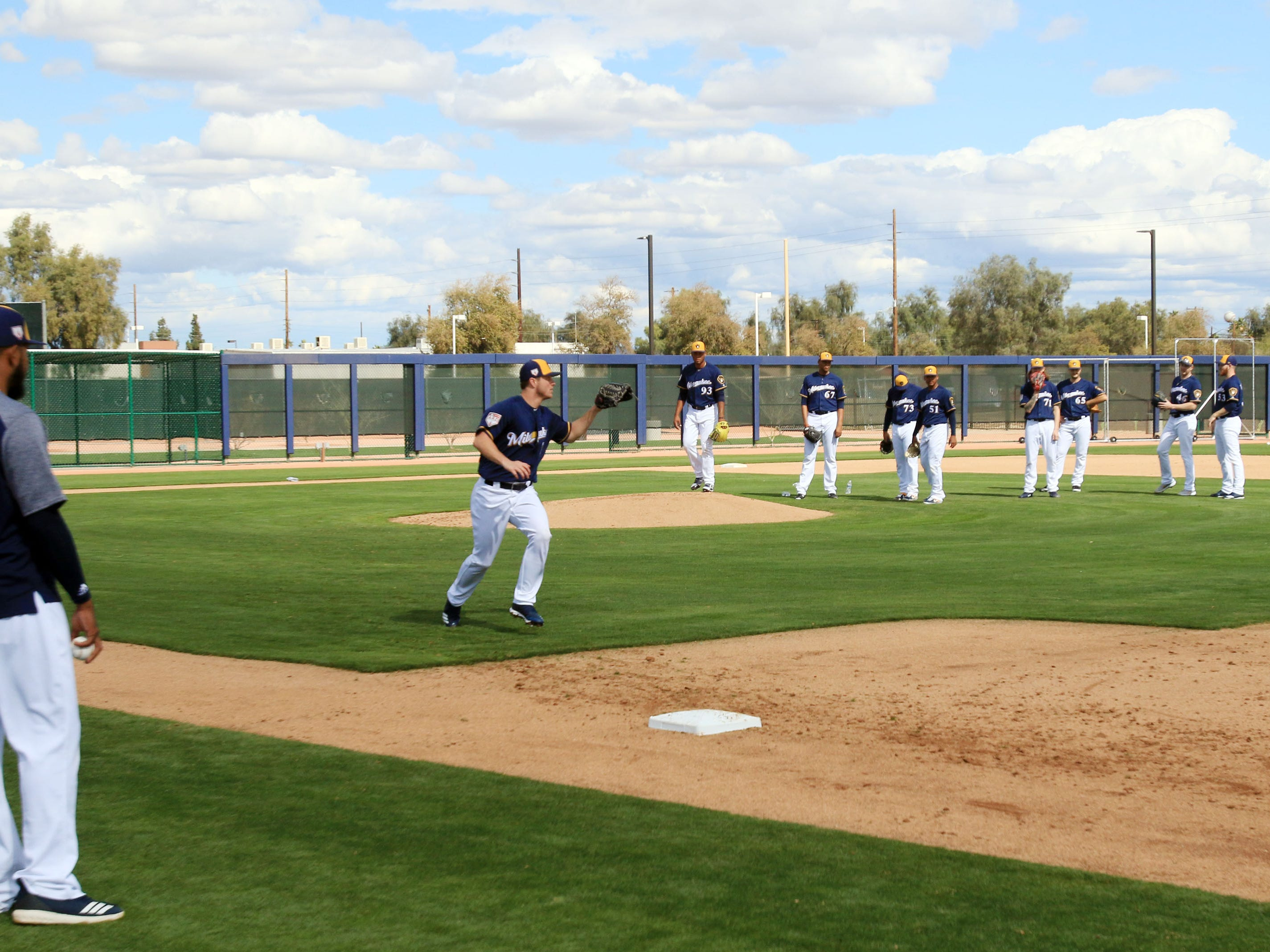 Brewers pitchers work on covering first base during drills on Saturday.