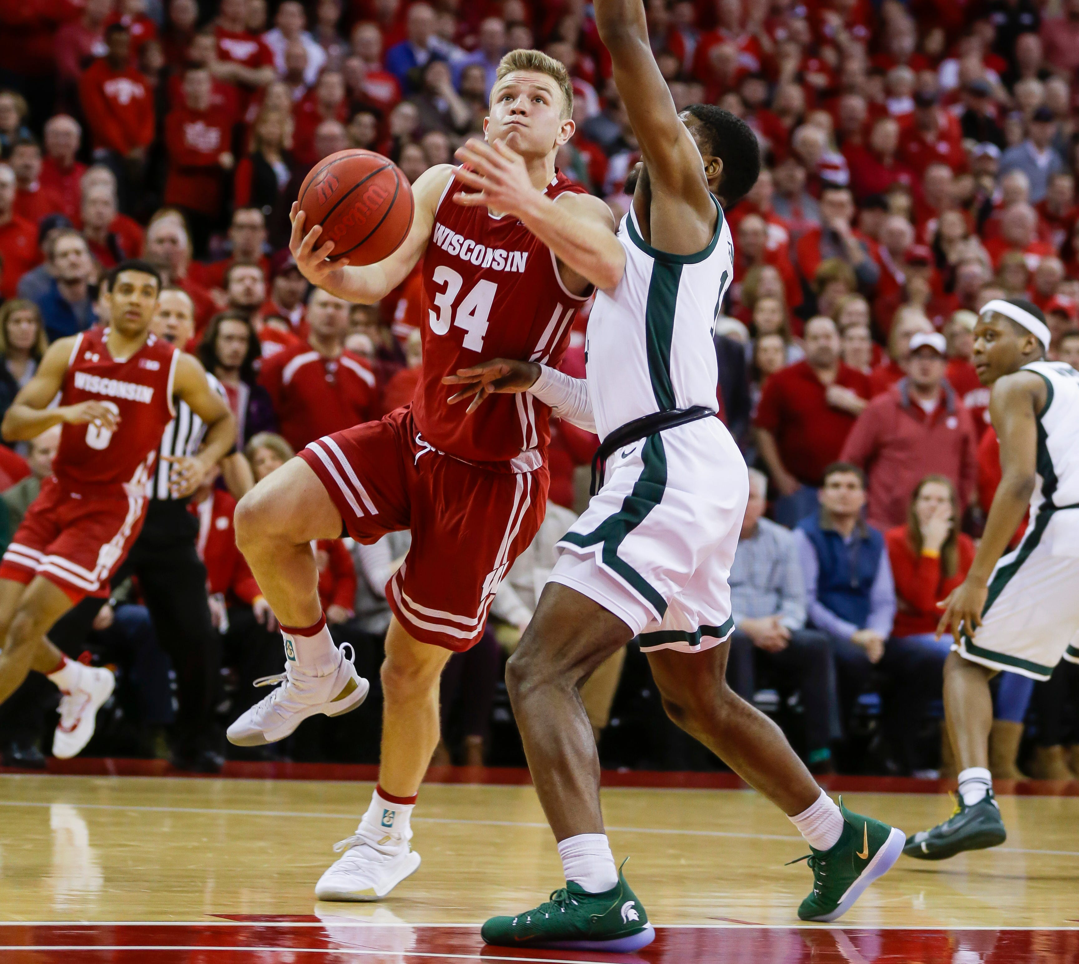 Wisconsin's Brad Davison (34) and Michigan States's Aaron Henry (11) during the second half of an NCAA college basketball game Tuesday, Feb. 12, 2019, in Madison, Wis. Michigan State won 67-59. (AP Photo/Andy Manis) ORG XMIT: WIAM1