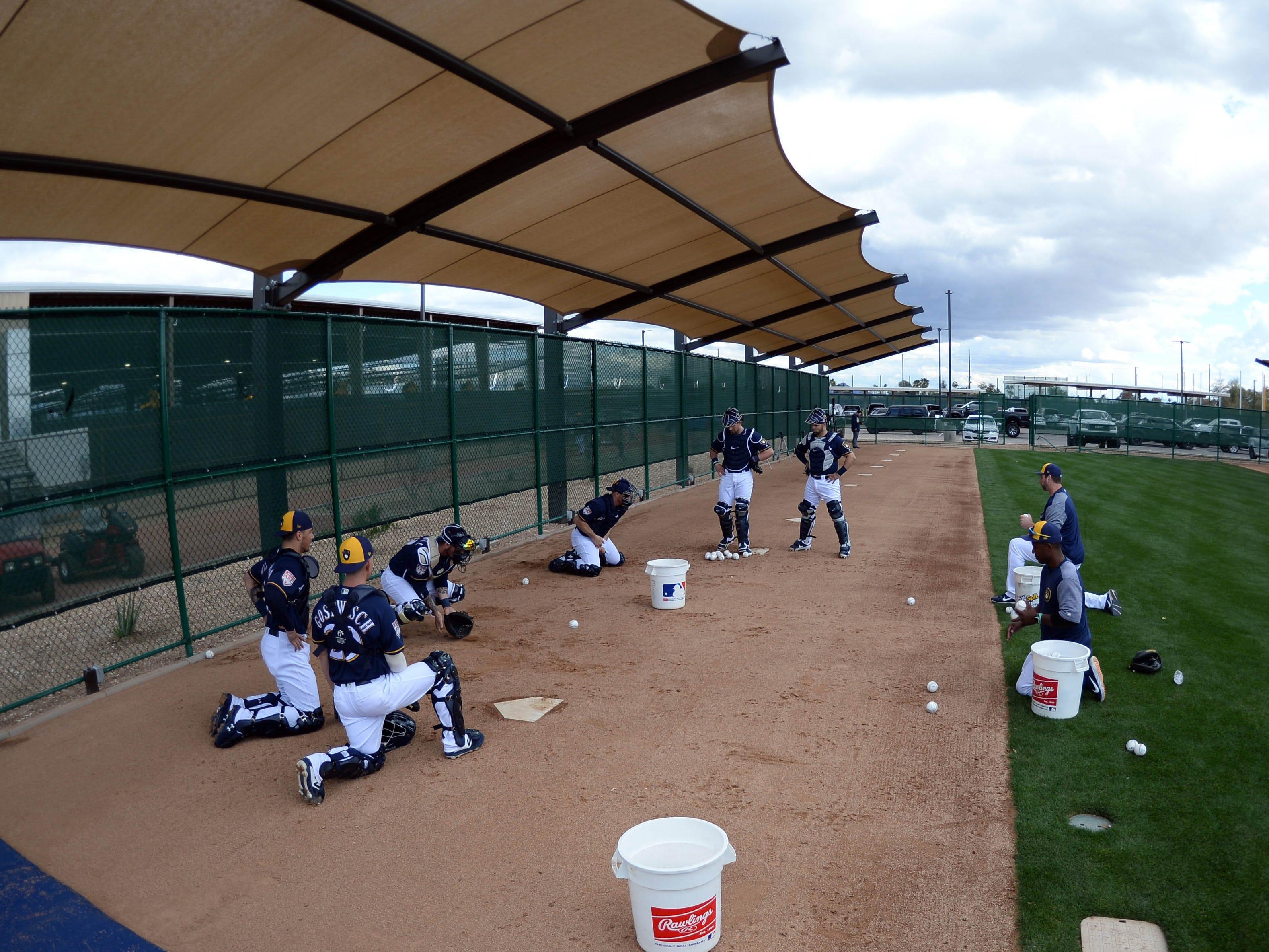 Brewers catchers work on blocking balls during drills Saturday.