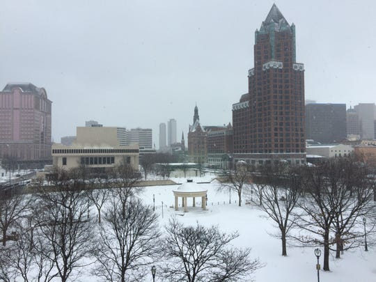 Snow falls on Pere Marquette Park in downtown Milwaukee Sunday morning.